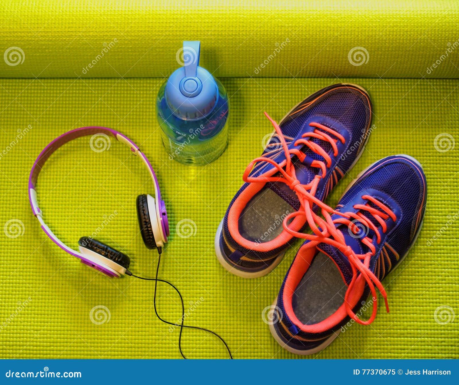 Яркие ботинки, наушники и бутылка с водой на свернутой ...