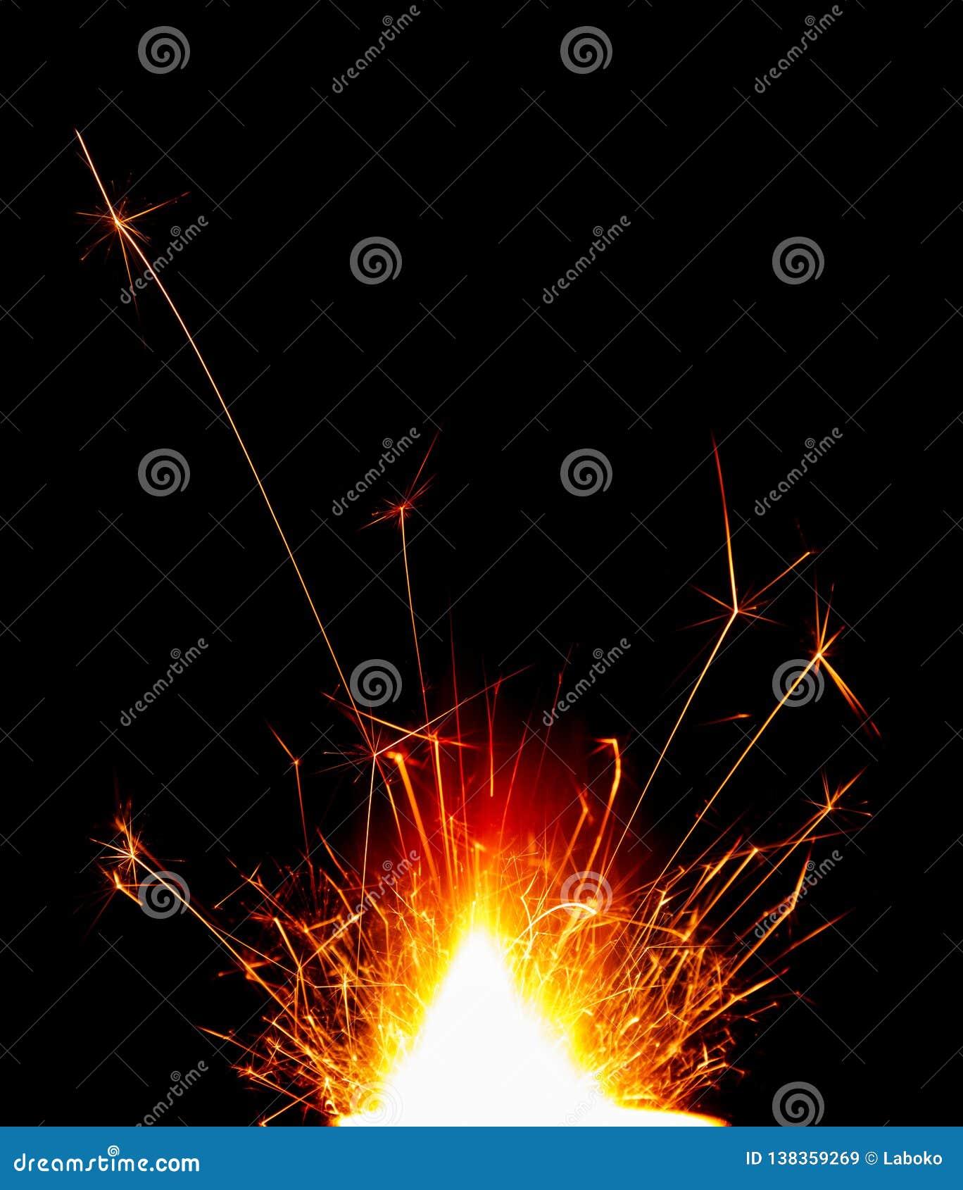 Яркий красивый бенгальский огонь праздника изолированный на черноте