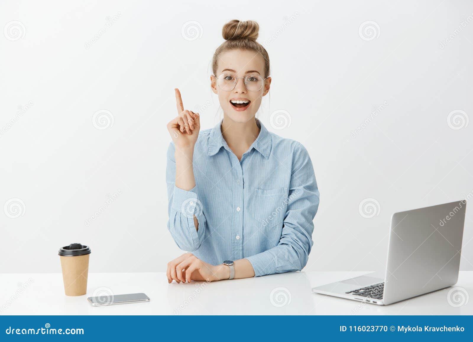 Я имею отличную идею Умный привлекательный женский менеджер офиса в стильных стеклах, сидящ около компьтер-книжки и smartphone