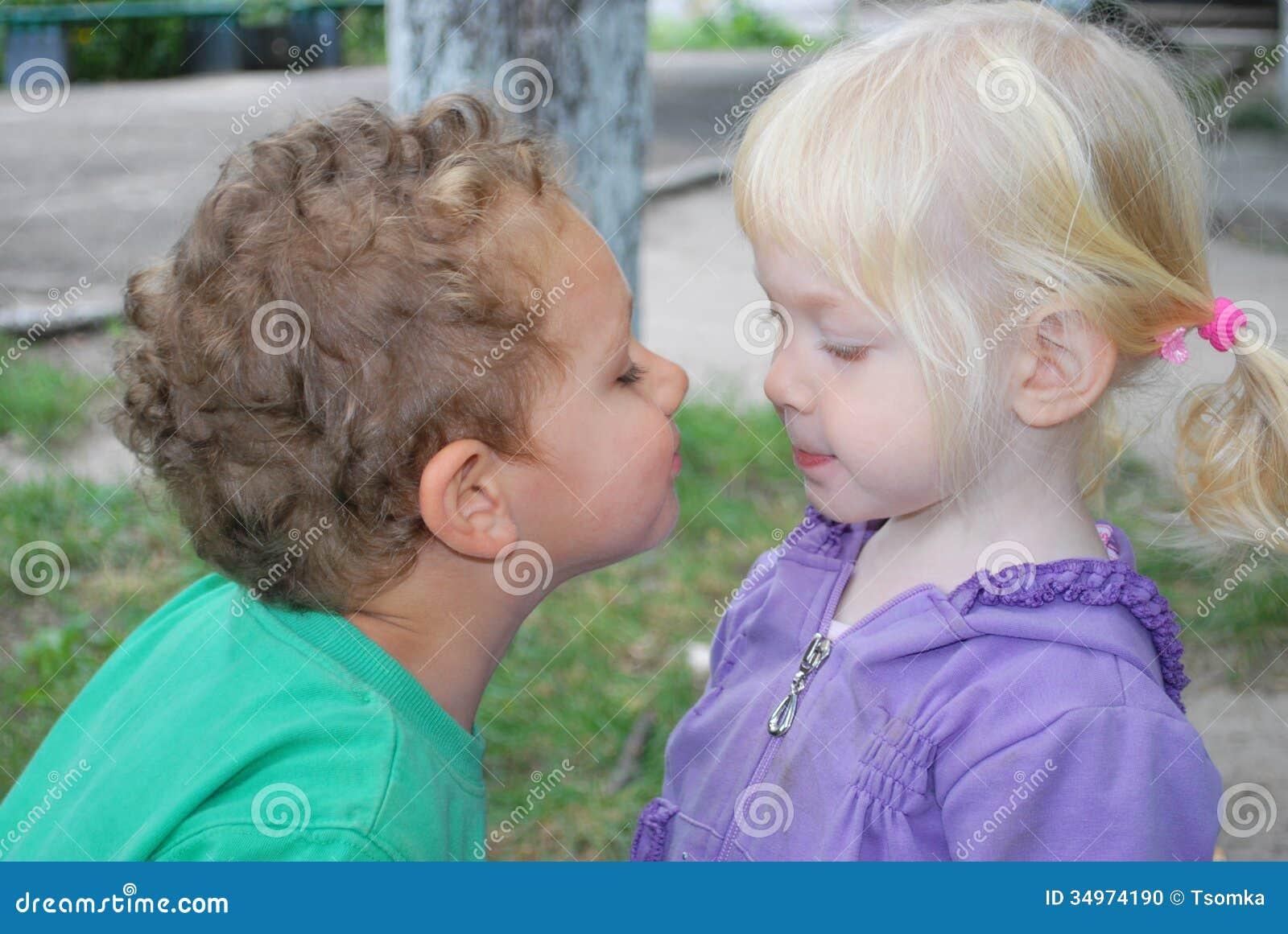 小女孩要亲吻男孩 库存照片