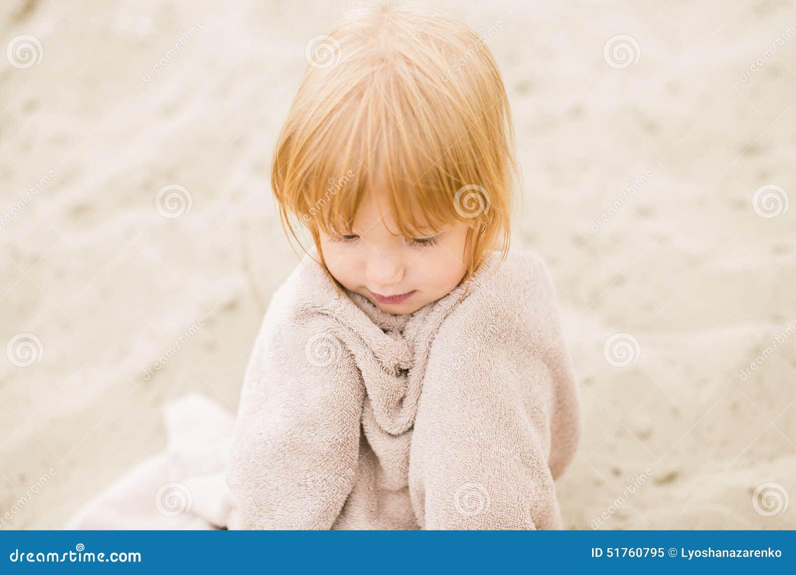 有红色头发的小女孩在海滩的一块毛巾图片