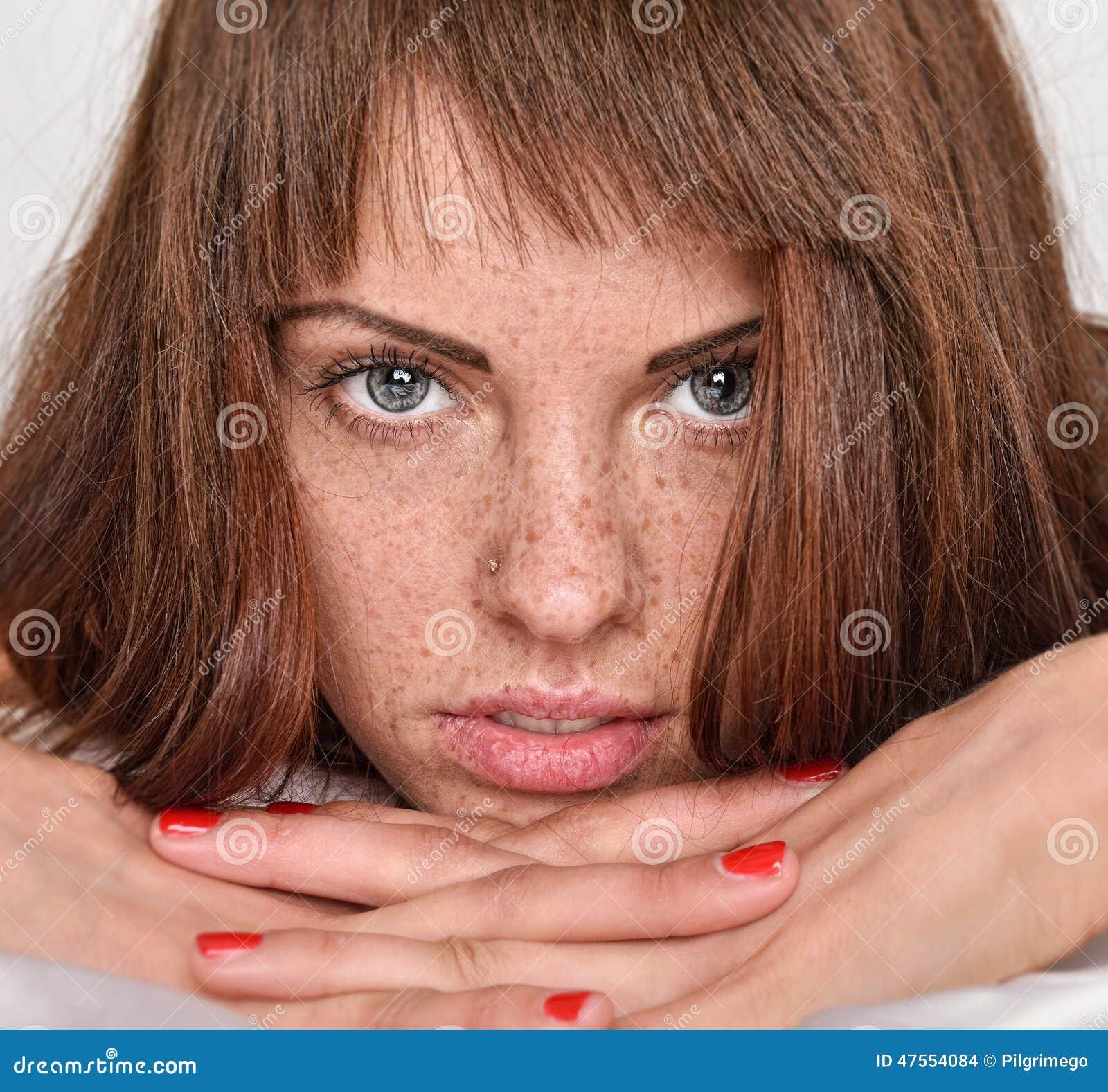 有红色头发和雀斑的美丽的妇女在床上