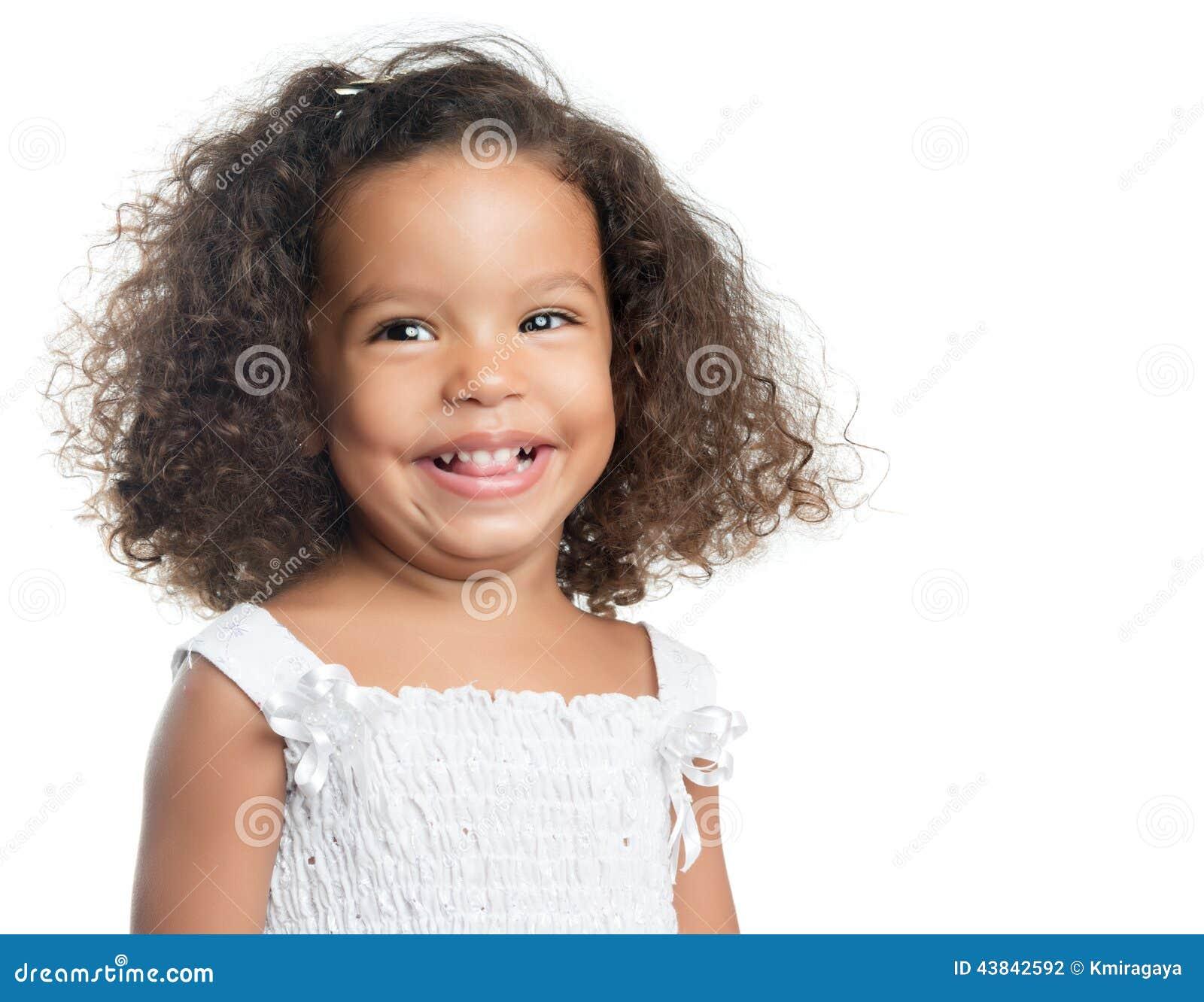 有一种非洲的发型的小女孩微笑和穿一件白色礼服的