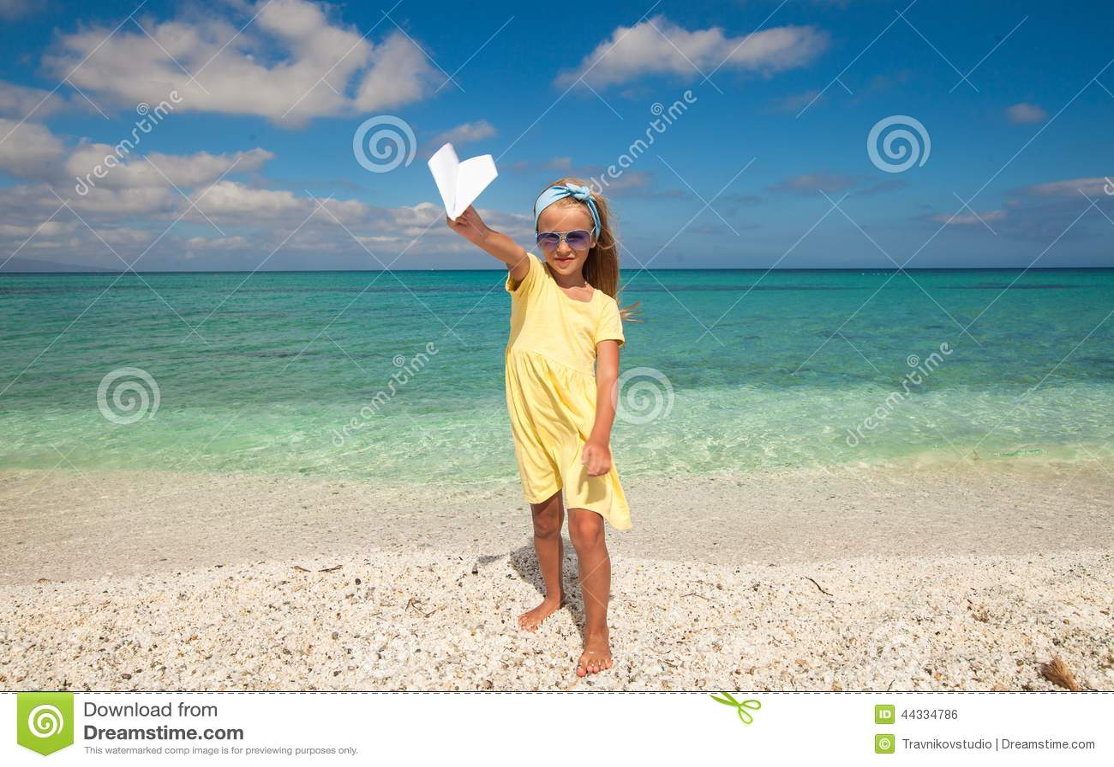 有纸飞机的可爱的小女孩在手上