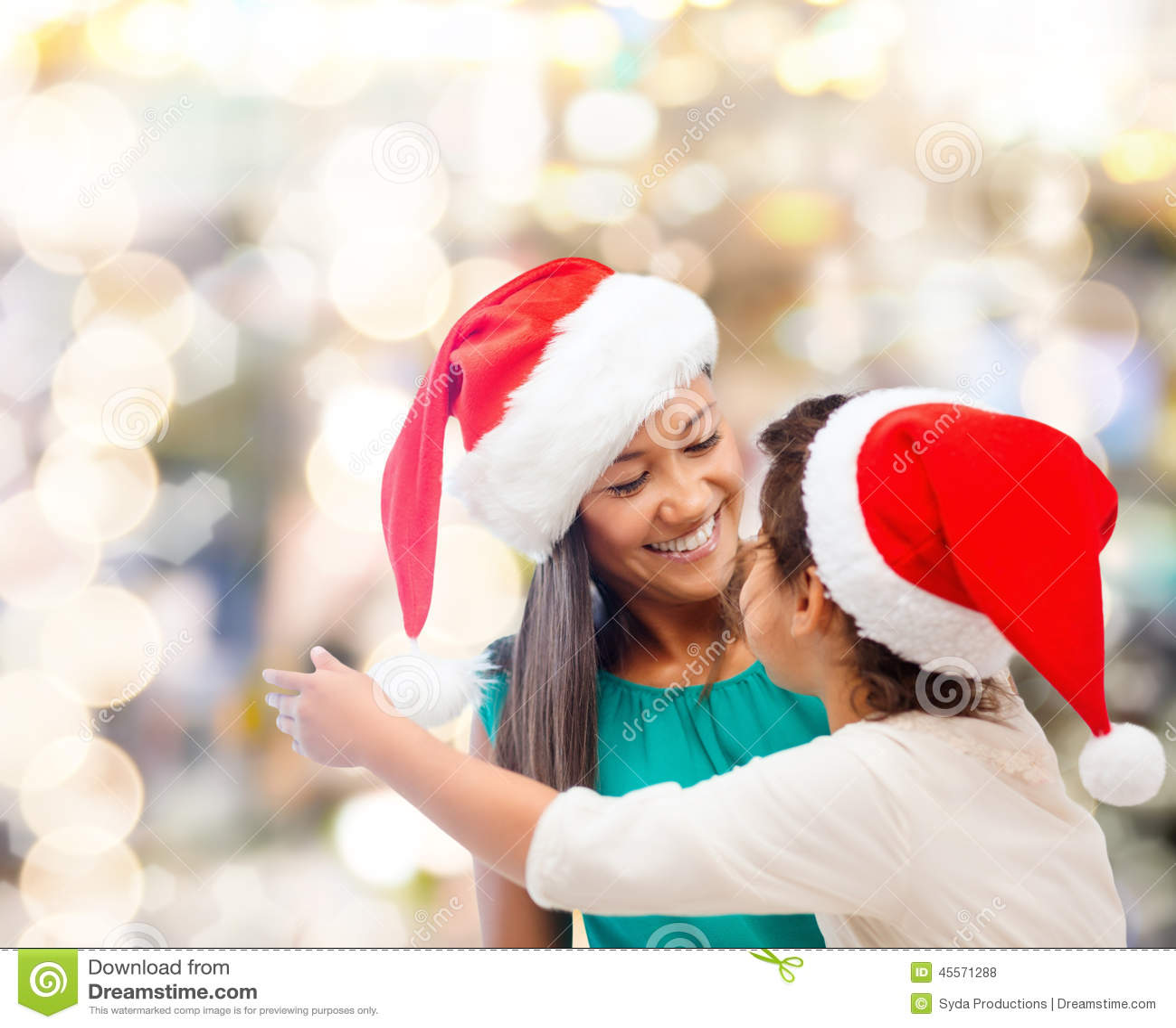 愉快的母亲和女孩圣诞老人帽子的