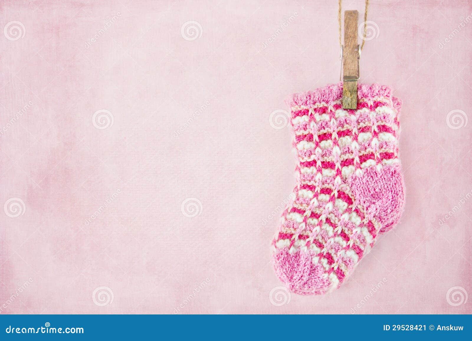 在粉红彩笔背景的女婴袜子