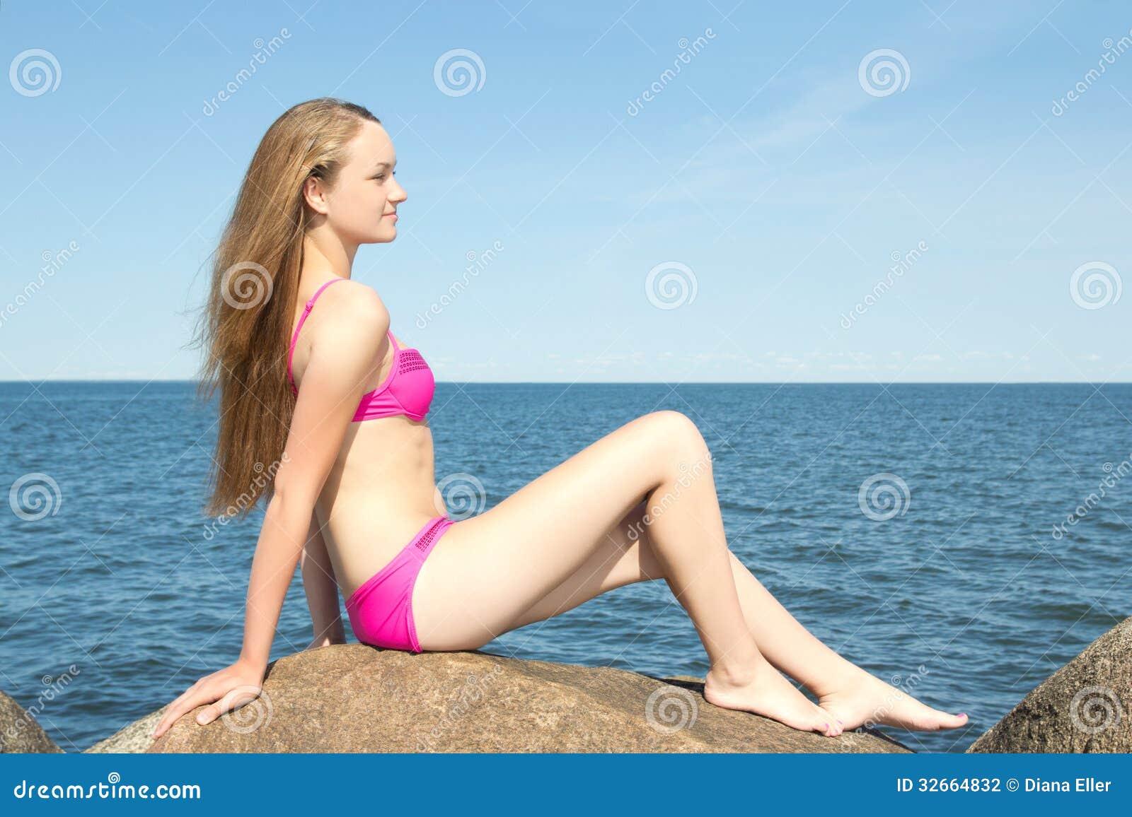 在桃红色比基尼泳装的美好的亭亭玉立的模型坐石头在