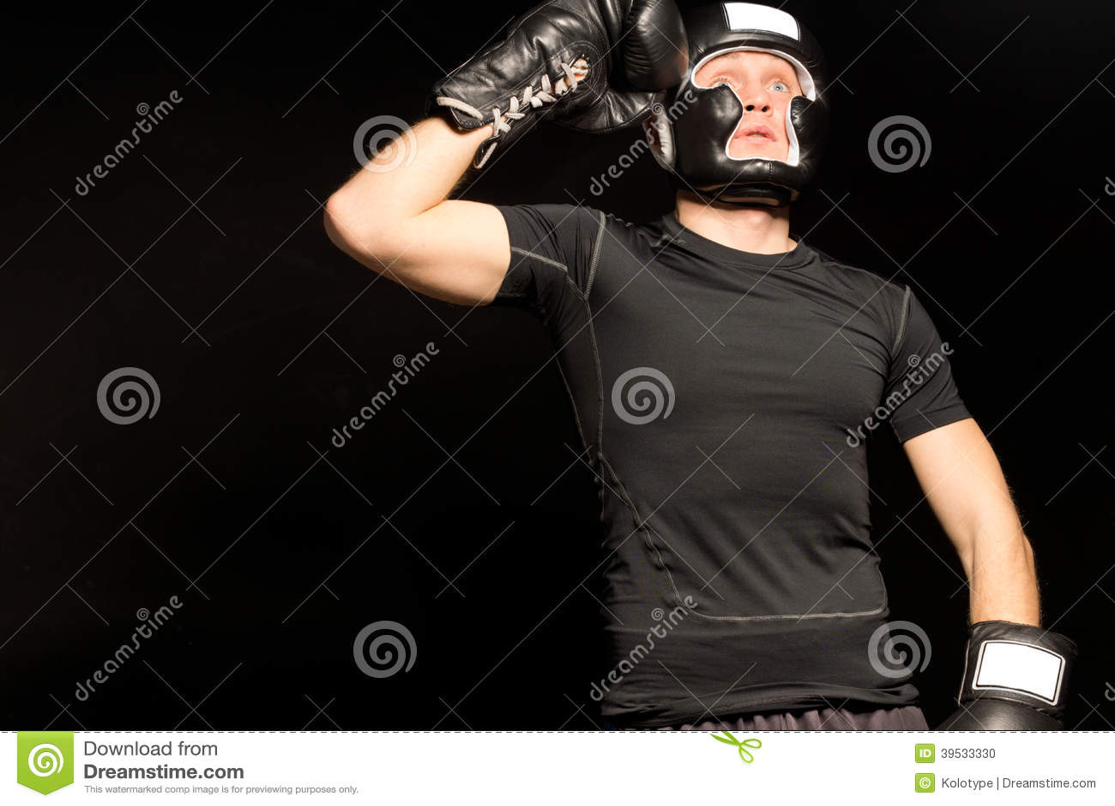 站立的拳击手举他的拳头对他的头,他查寻入与一个强烈的表示的空气在