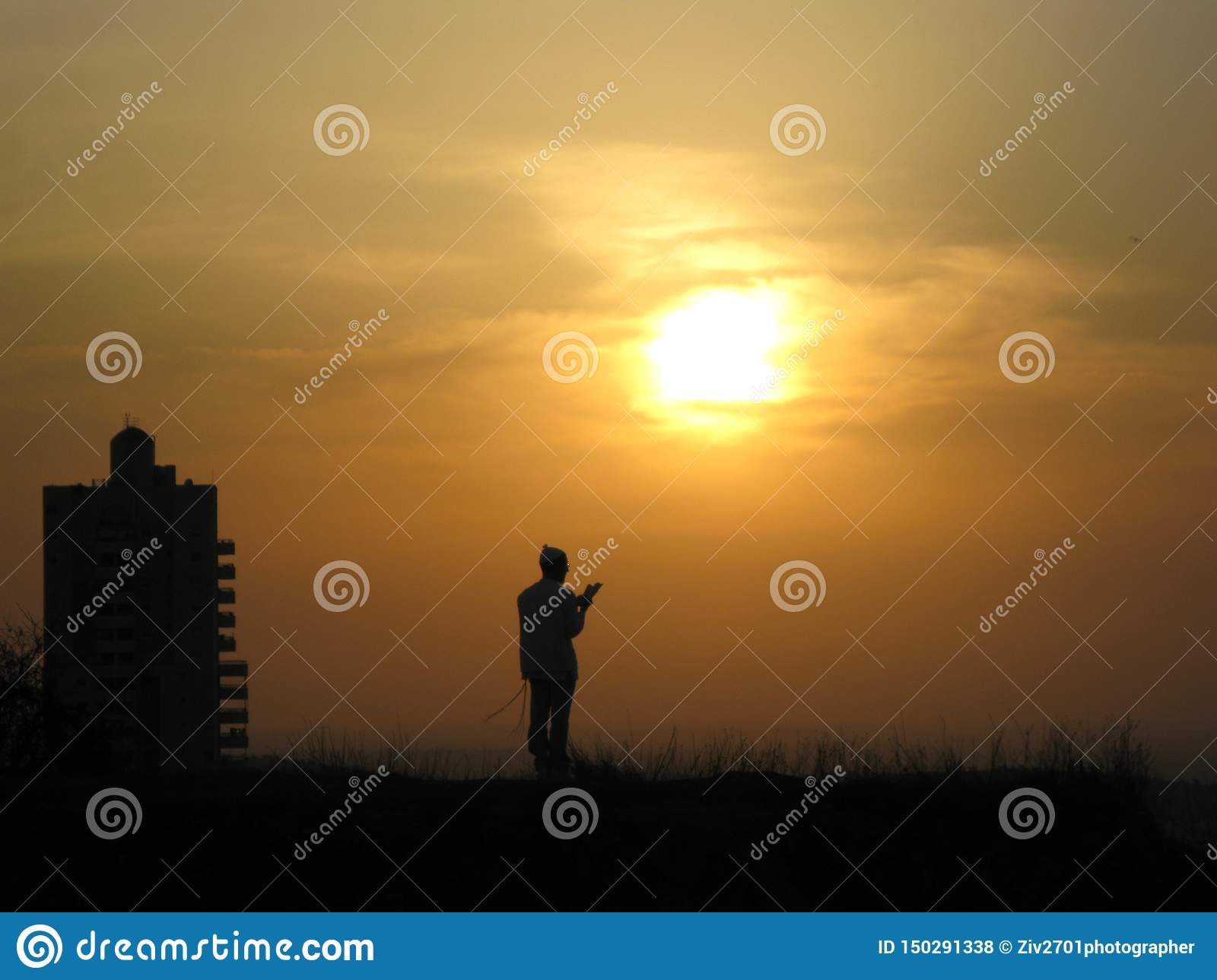 A religious person prays to God on a hill in front of the sun and sunset