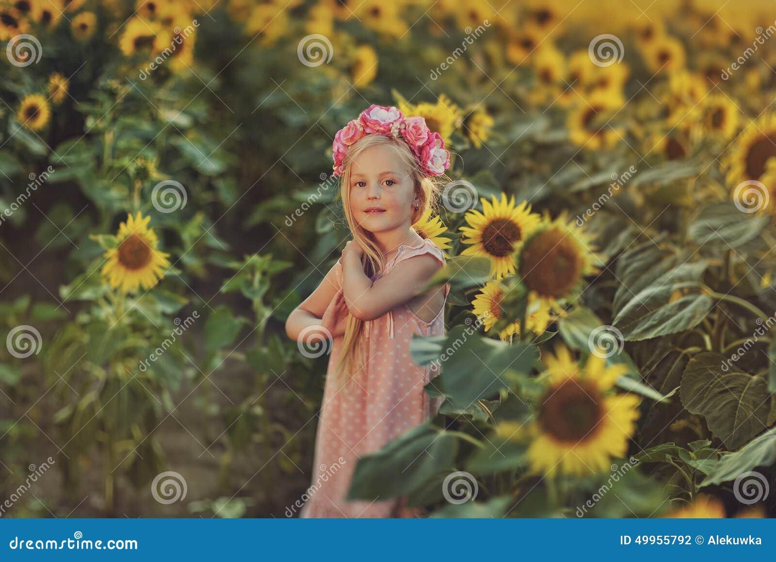 有长的头发的小女孩在一件桃红色礼服和一个花圈在他的头在向日葵.图片