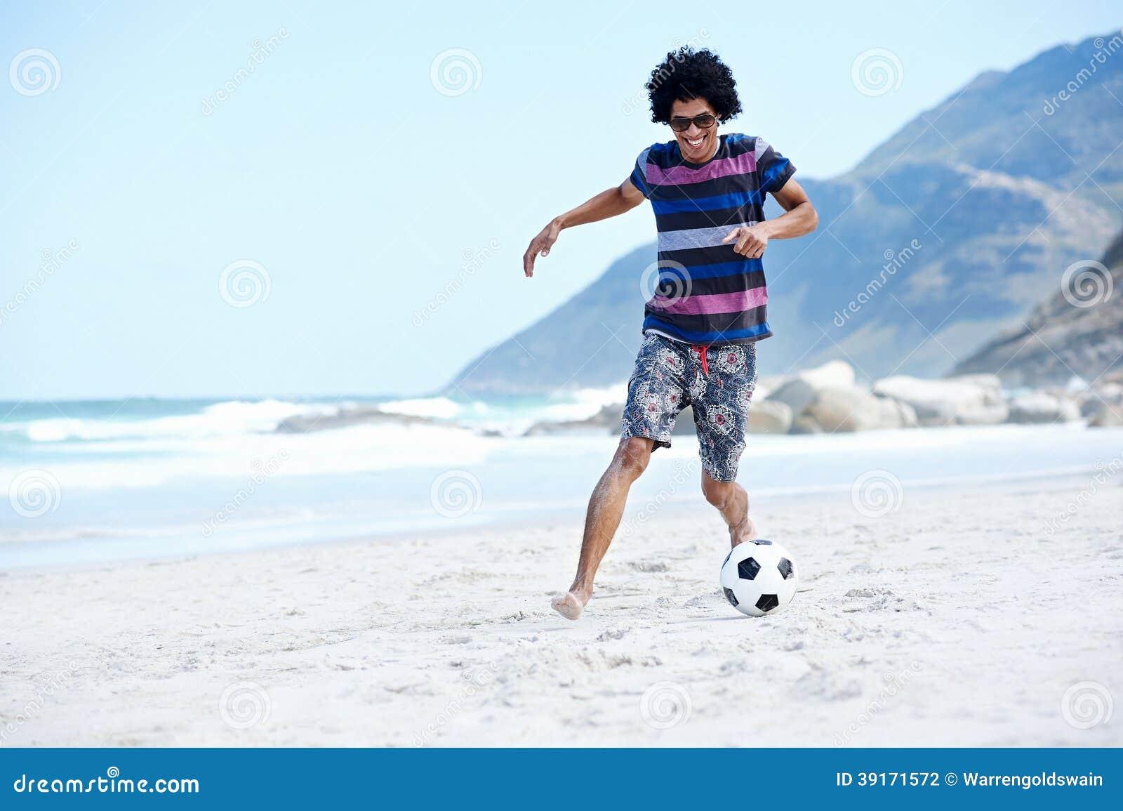 拉美裔踢在海滩与一滴技巧和球的巴西人足球在度假.图片