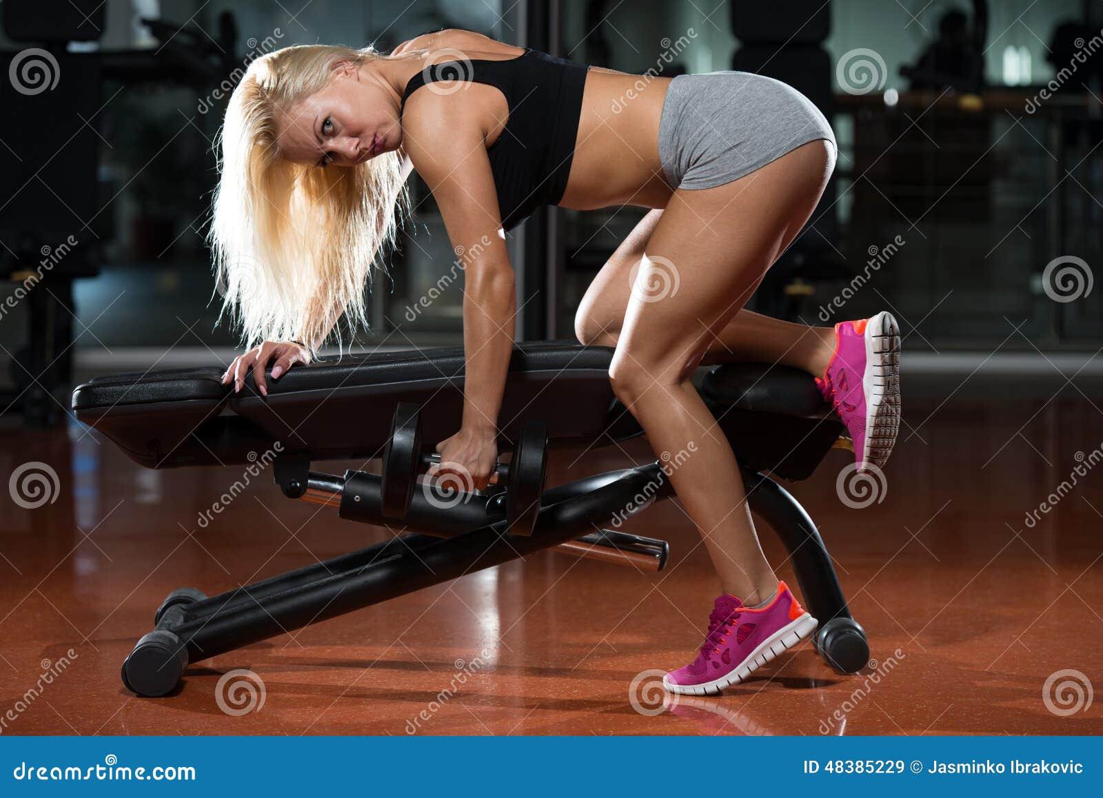 做在健身房的年轻女性背部锻炼