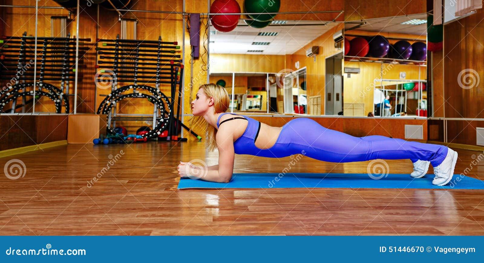 做在席子的健身房的女孩锻炼