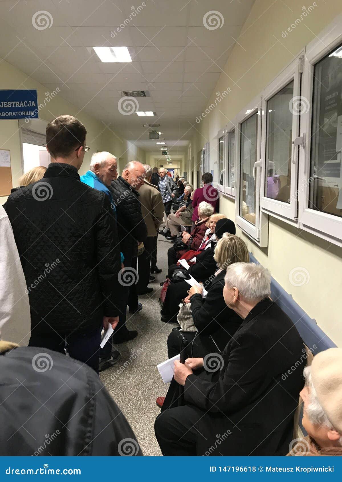 'Aw WrocÅ, Польша - 6-ое мая 2019: Пациенты общественного здравоохранения ждать в длинной очереди к комнате регистрации Линия нас
