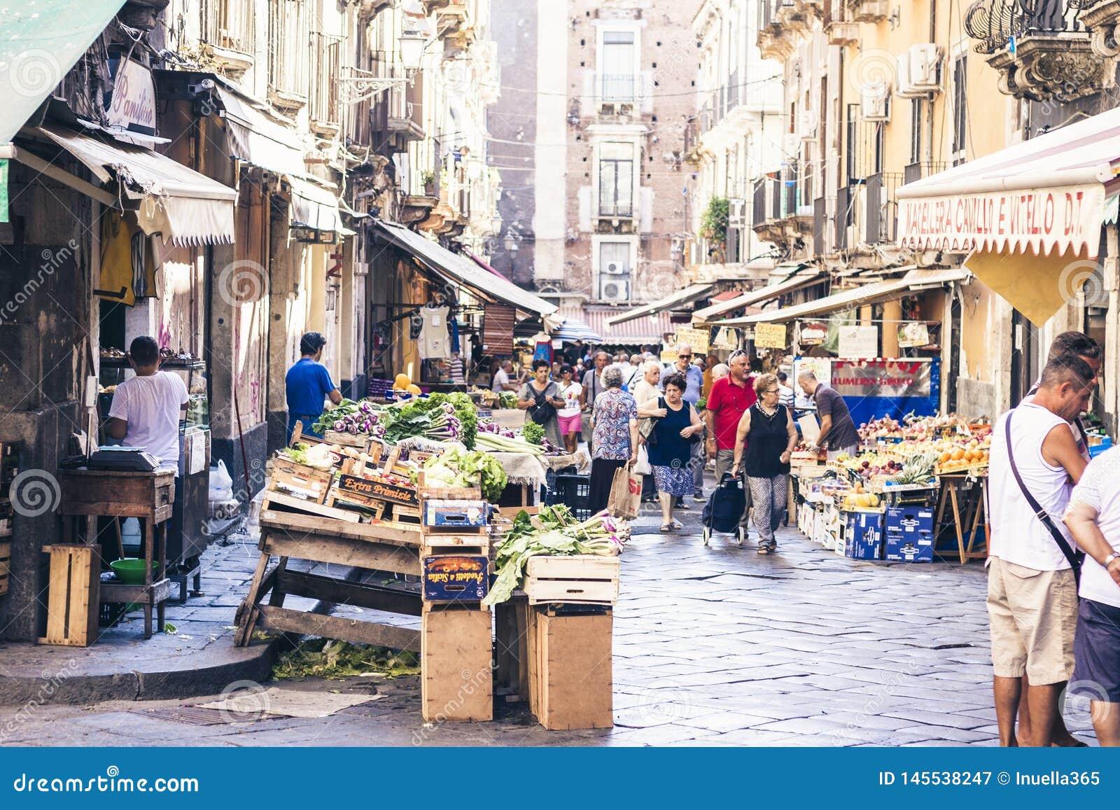 € «16-ое августа 2018 Катании, Сицилии, Италии: рыночная площадь с людьми которые покупая овощи и плоды