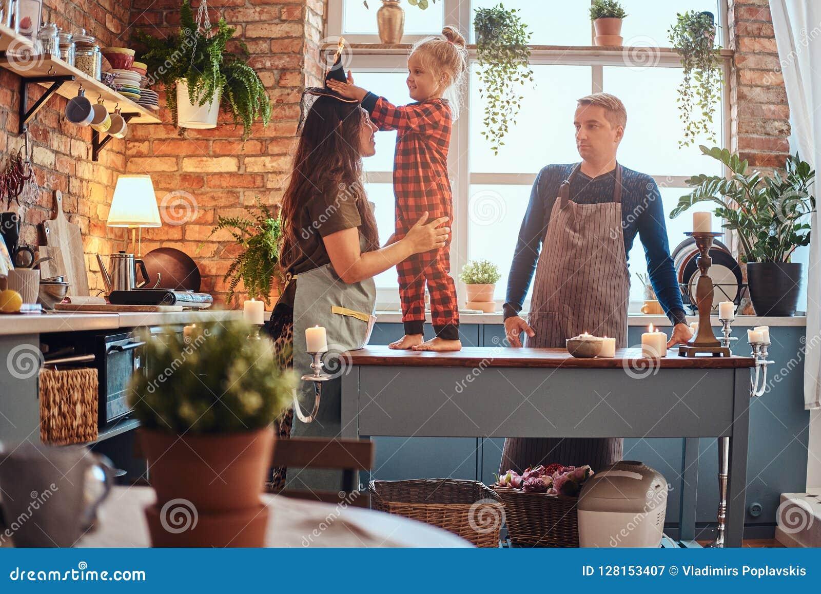 一个不可思议的帽子在顶楼样式厨房朝向在早晨的小女孩站立在桌上的在她的妈妈的和礼服
