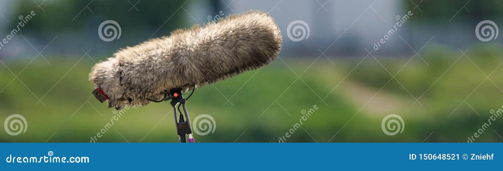 一个专业话筒的特写镜头录音的以减少风噪声的盖子,故意地被弄脏的背景,