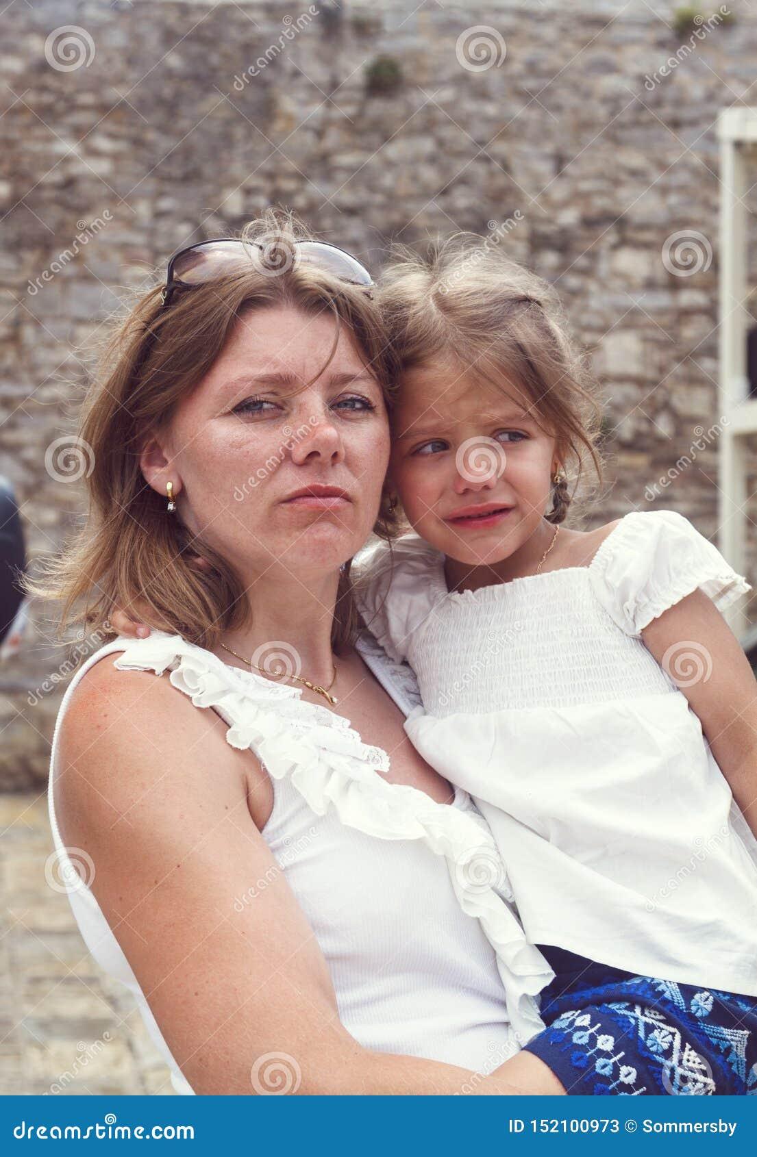一个严肃和严密的母亲拿着调查t的一个震惊的女孩