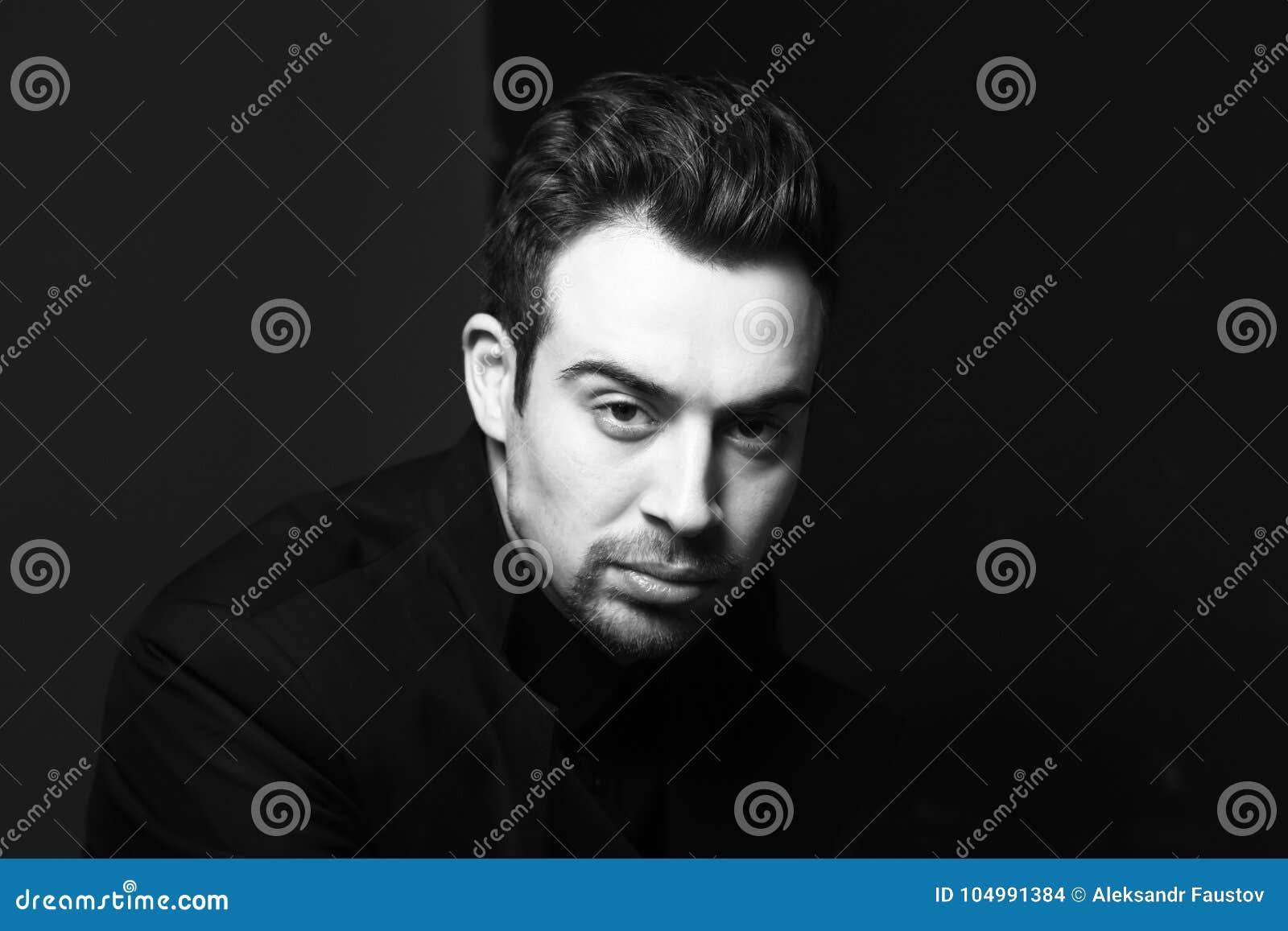 一个严肃的年轻英俊的人的黑白画象在黑,剧烈的照明设备穿戴了