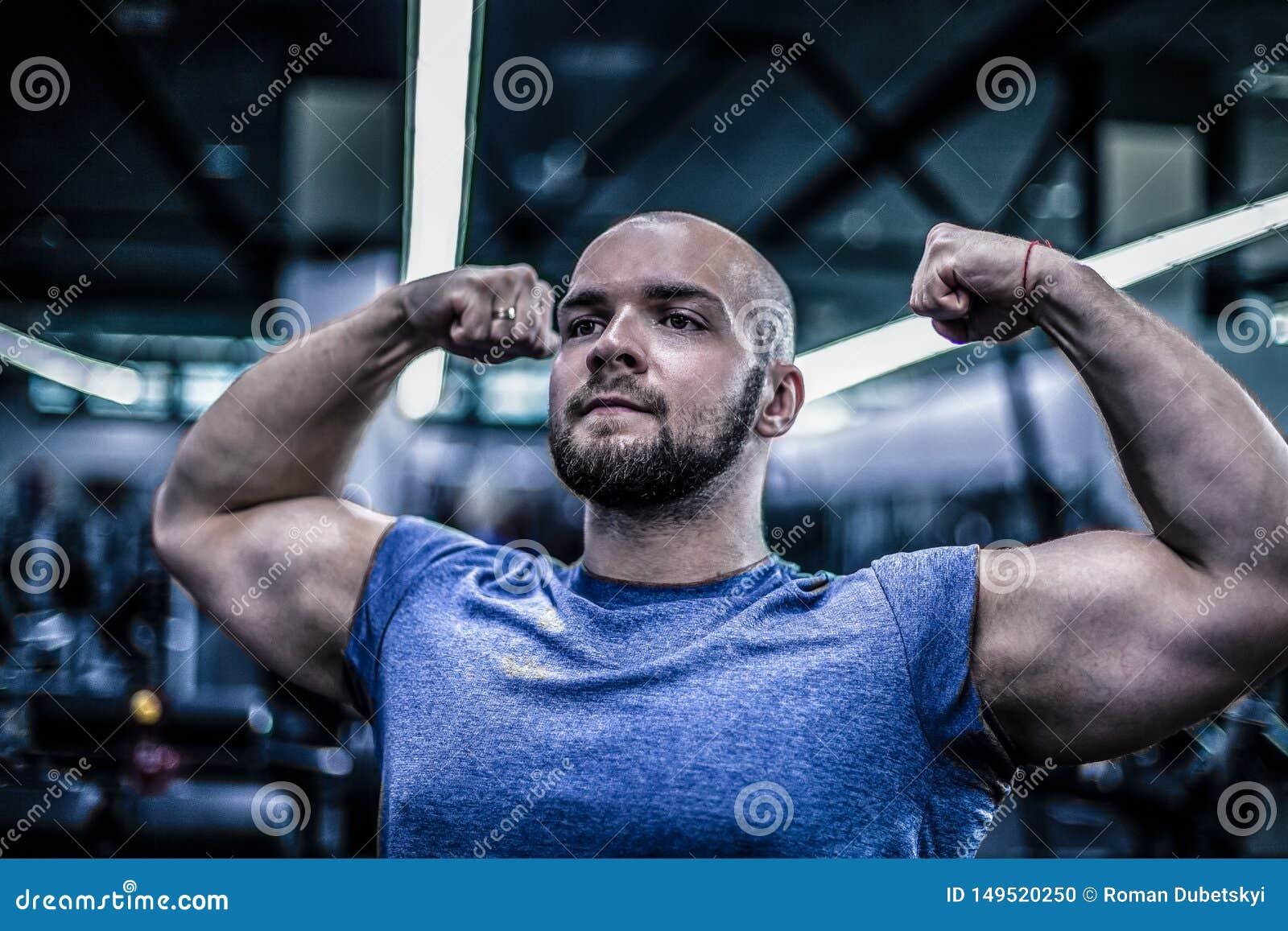 一个严肃的爱好健美者的画象有一个秃头的 展示您的二头肌 锻炼是成功的