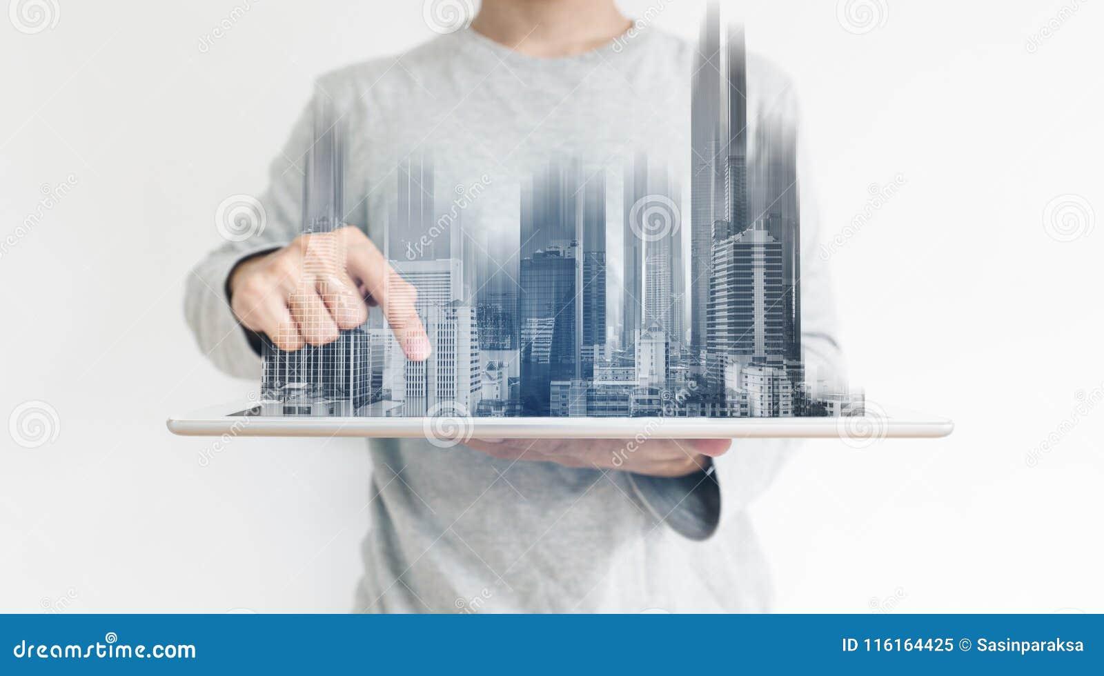 一个人使用数字式片剂的和现代大厦全息图 房地产事务和建筑技术概念