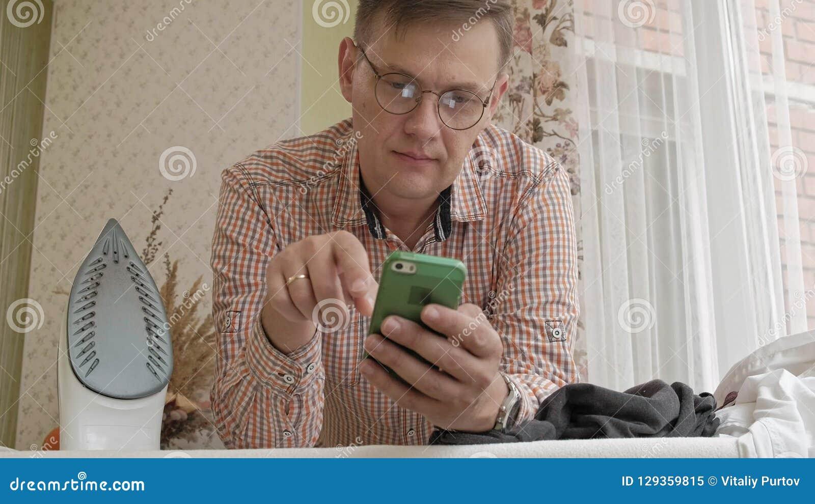 一个人在他的房子里抚摸他的在电烙板的衬衣并且使用智能手机 股票视频