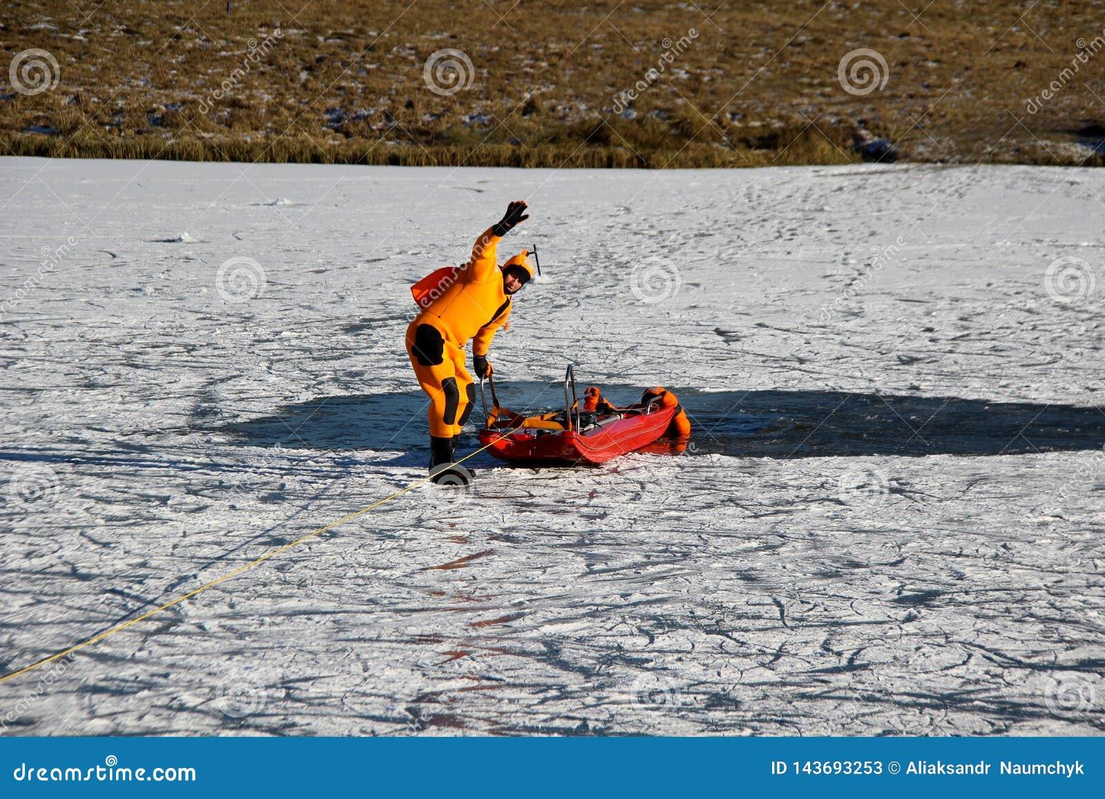 一个人在冰冷的水中淹没 一套特别衣服的一个人在一个冻湖淹没