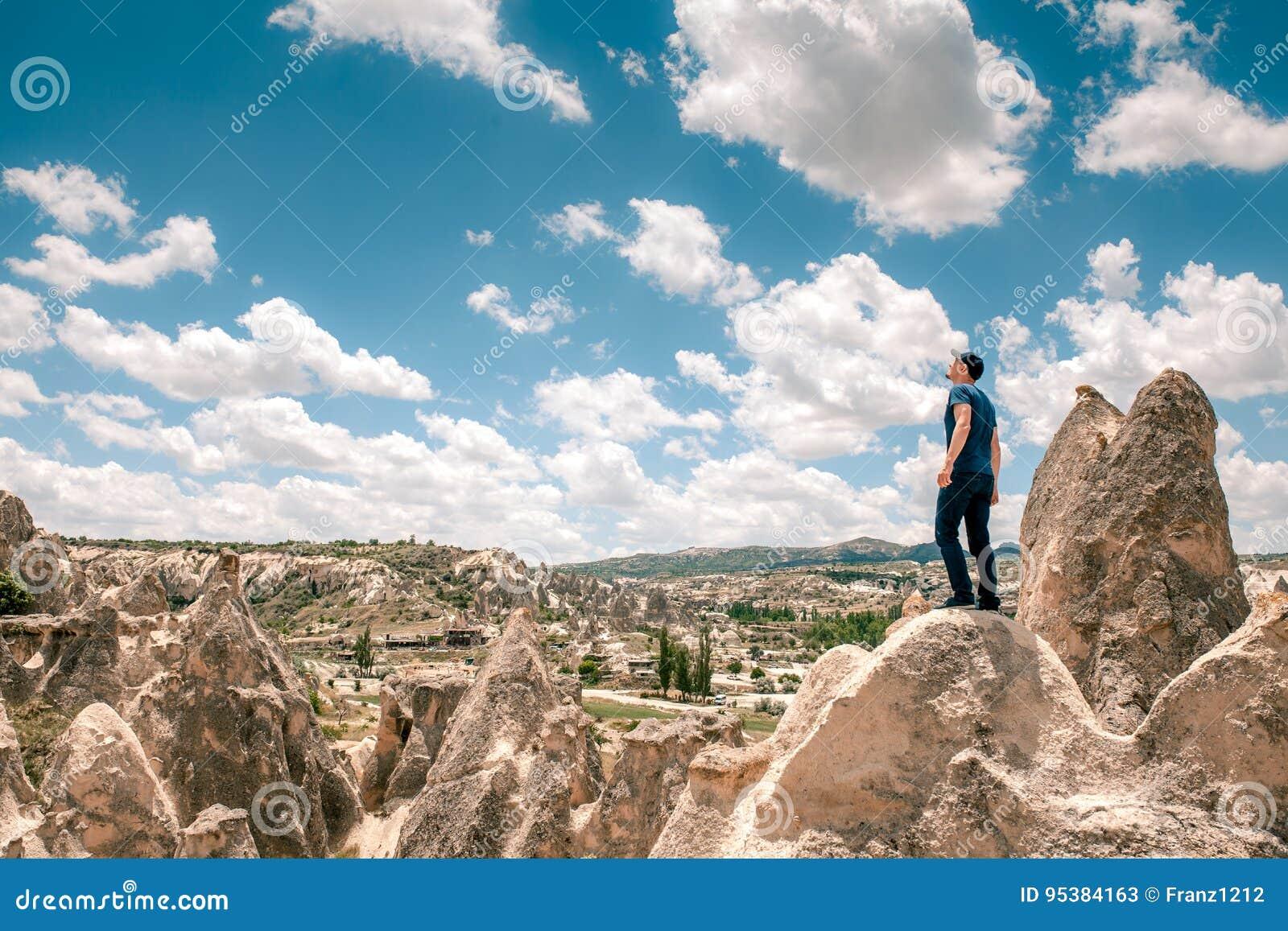一个人在小山顶部在卡帕多细亚在土耳其查寻对惊人的云彩 旅行,成功,自由,成就