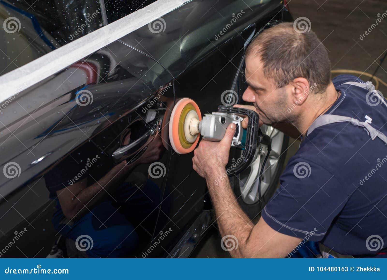一个人擦亮一辆黑汽车
