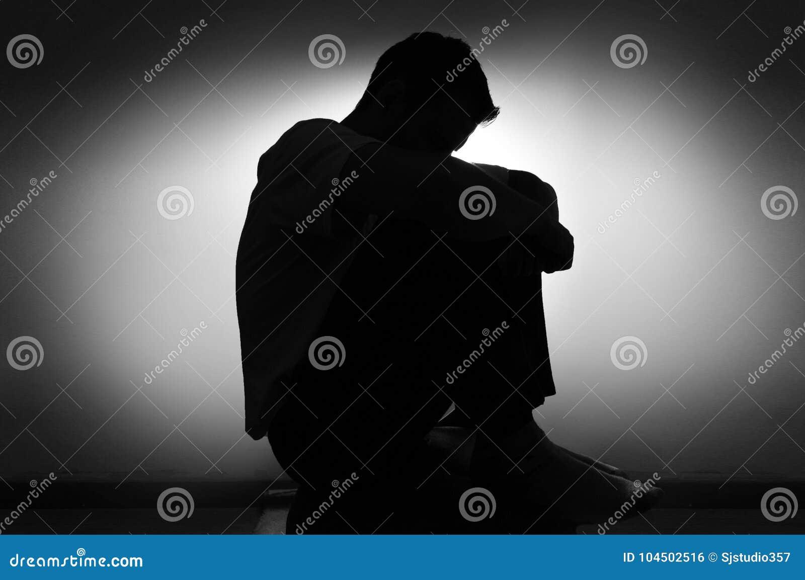 一个人的哀伤的剪影消沉的坐与下来他的头的一把椅子