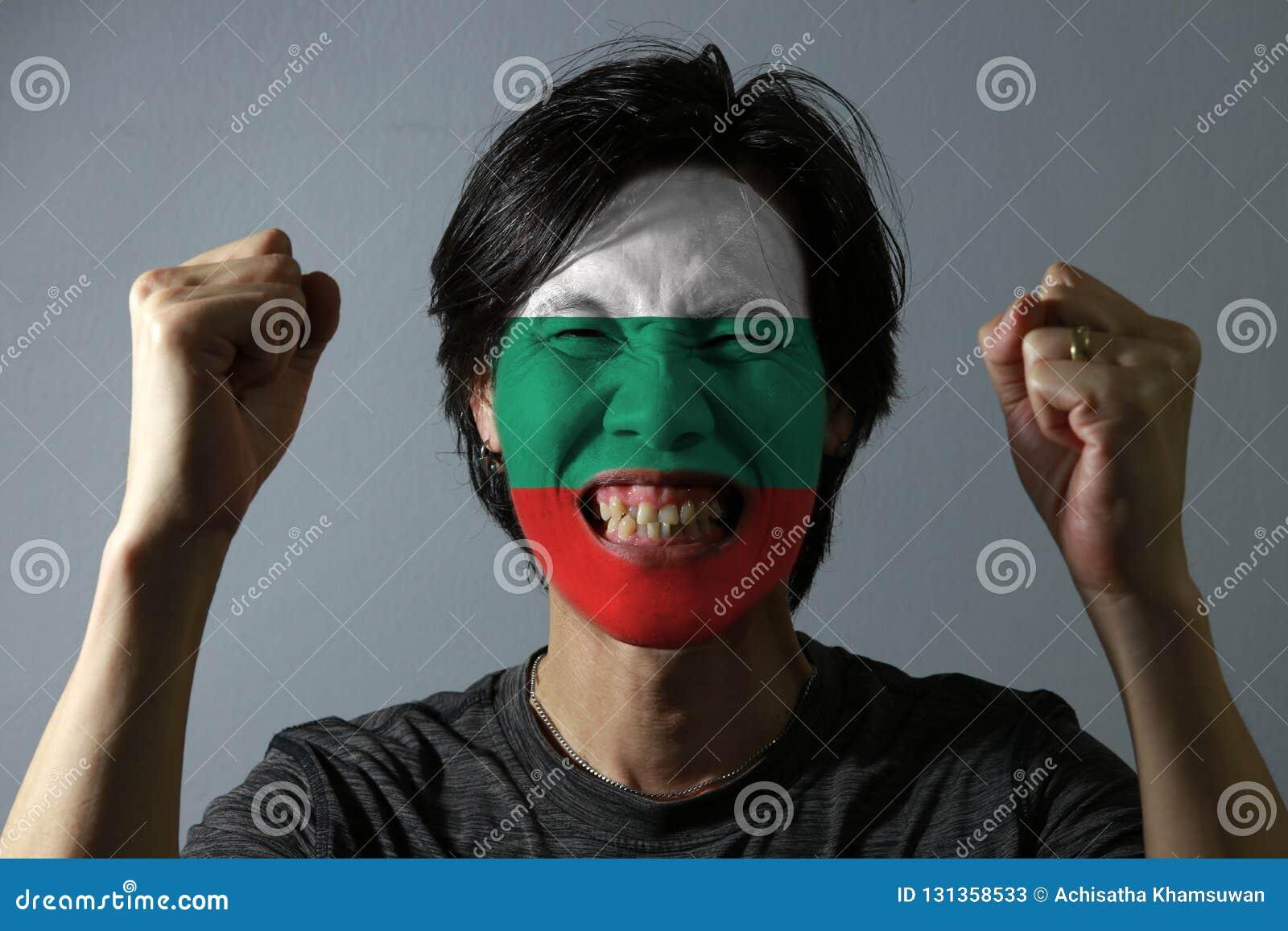 一个人的快乐的画象有保加利亚的旗子的在他的在灰色背景的面孔绘了
