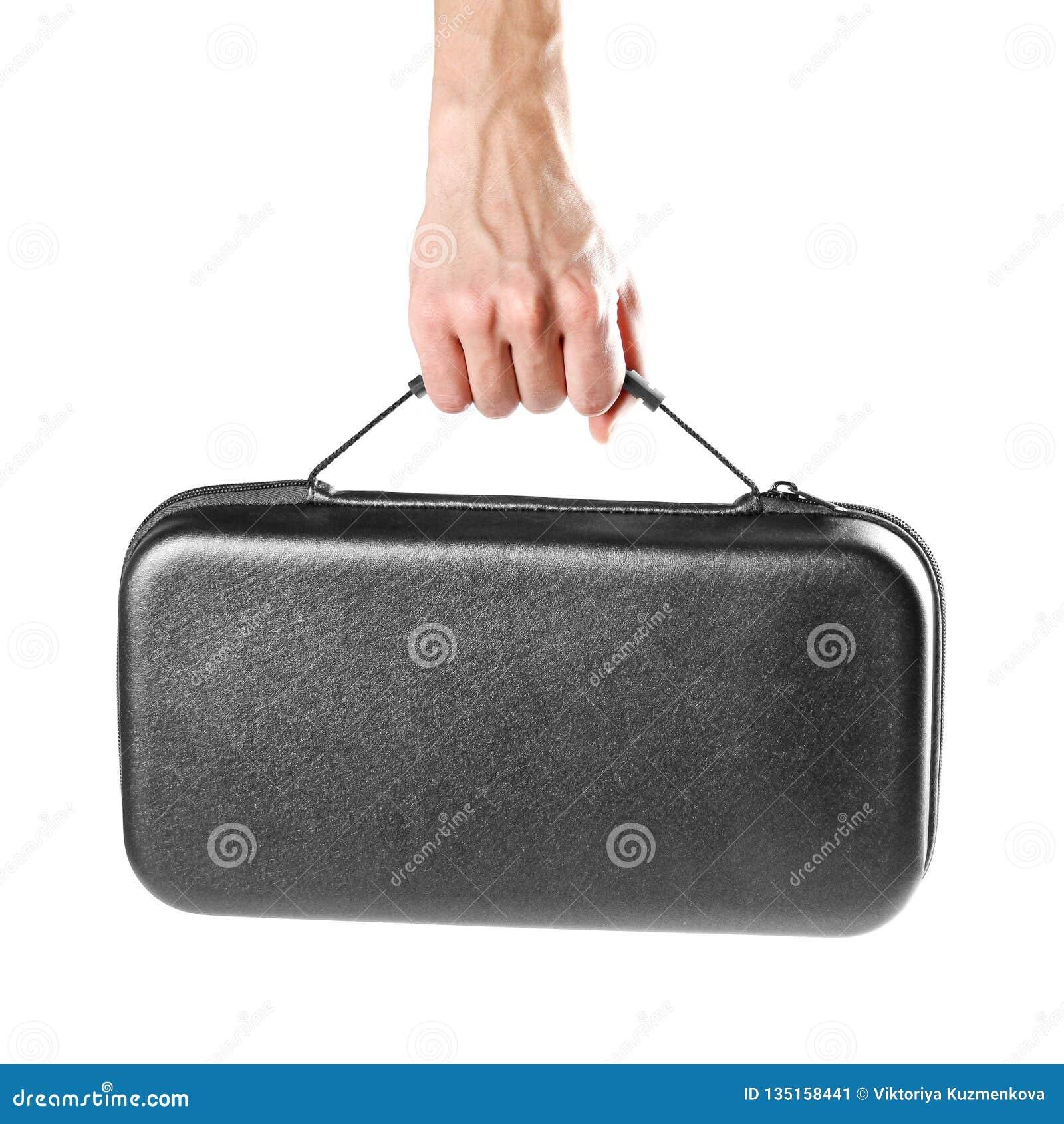 一个人的手拿着一个黑塑料手提箱 关闭 背景查出的白色
