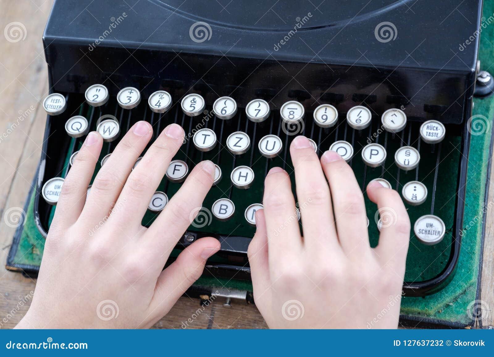 一个人的手的特写镜头键入在一台老打字机的