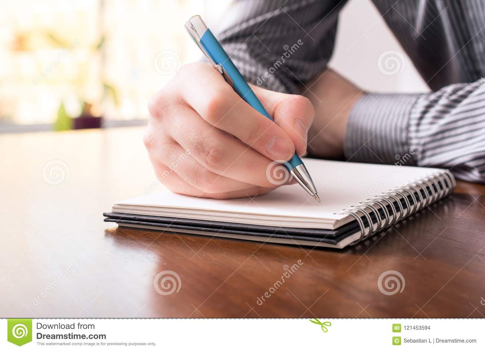 一个人的正面图企业衬衣文字的在与圆珠笔的一个空白的笔记薄