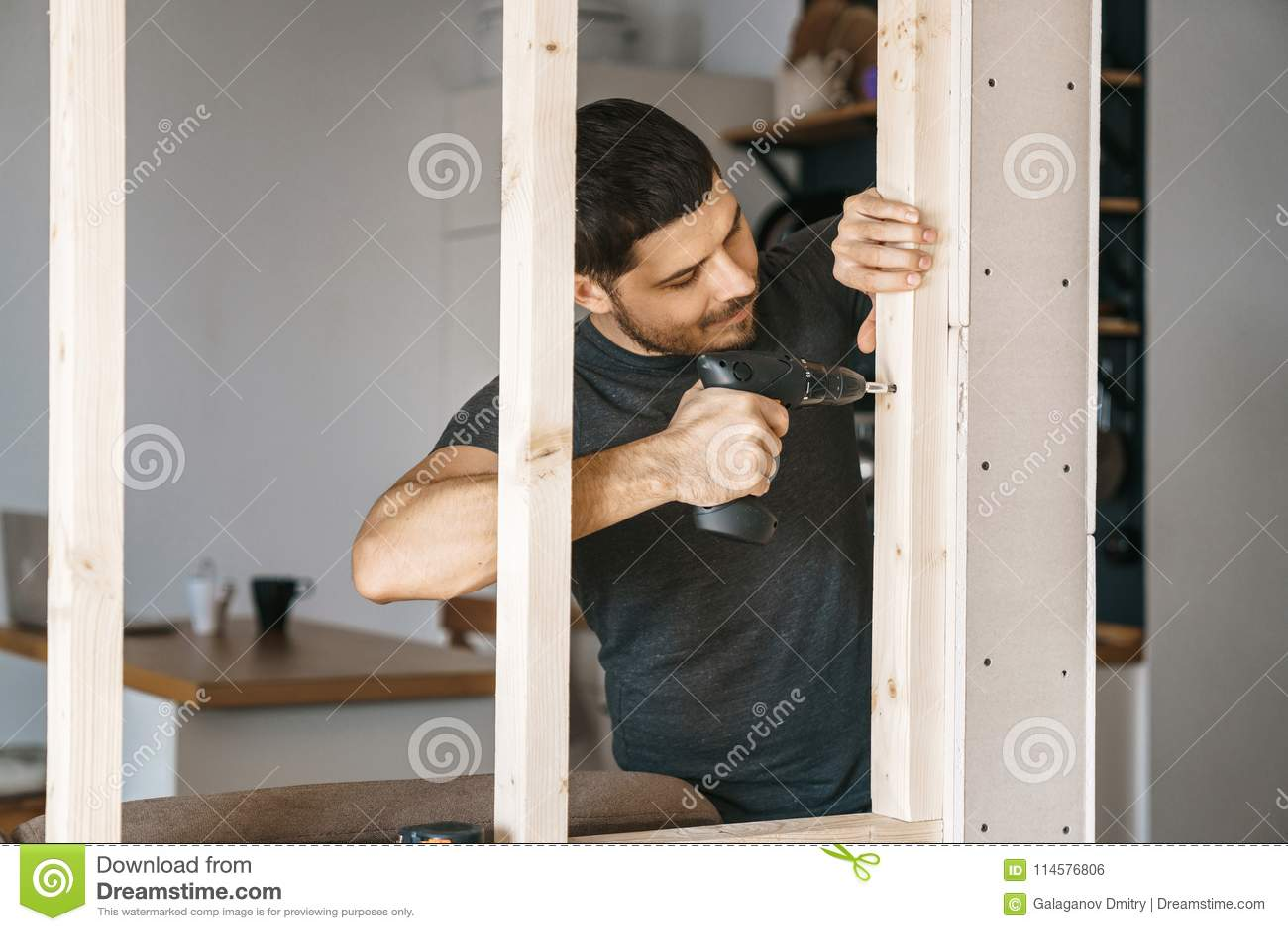 一个人的画象家庭衣裳的有一把螺丝刀的在他的手上在他的房子里修理一个窗口的木建筑 维修服务