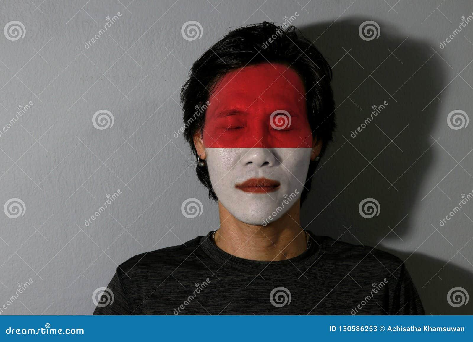一个人的画象有印度尼西亚的旗子的在他的面孔和接近的眼睛绘了与黑阴影在灰色背景