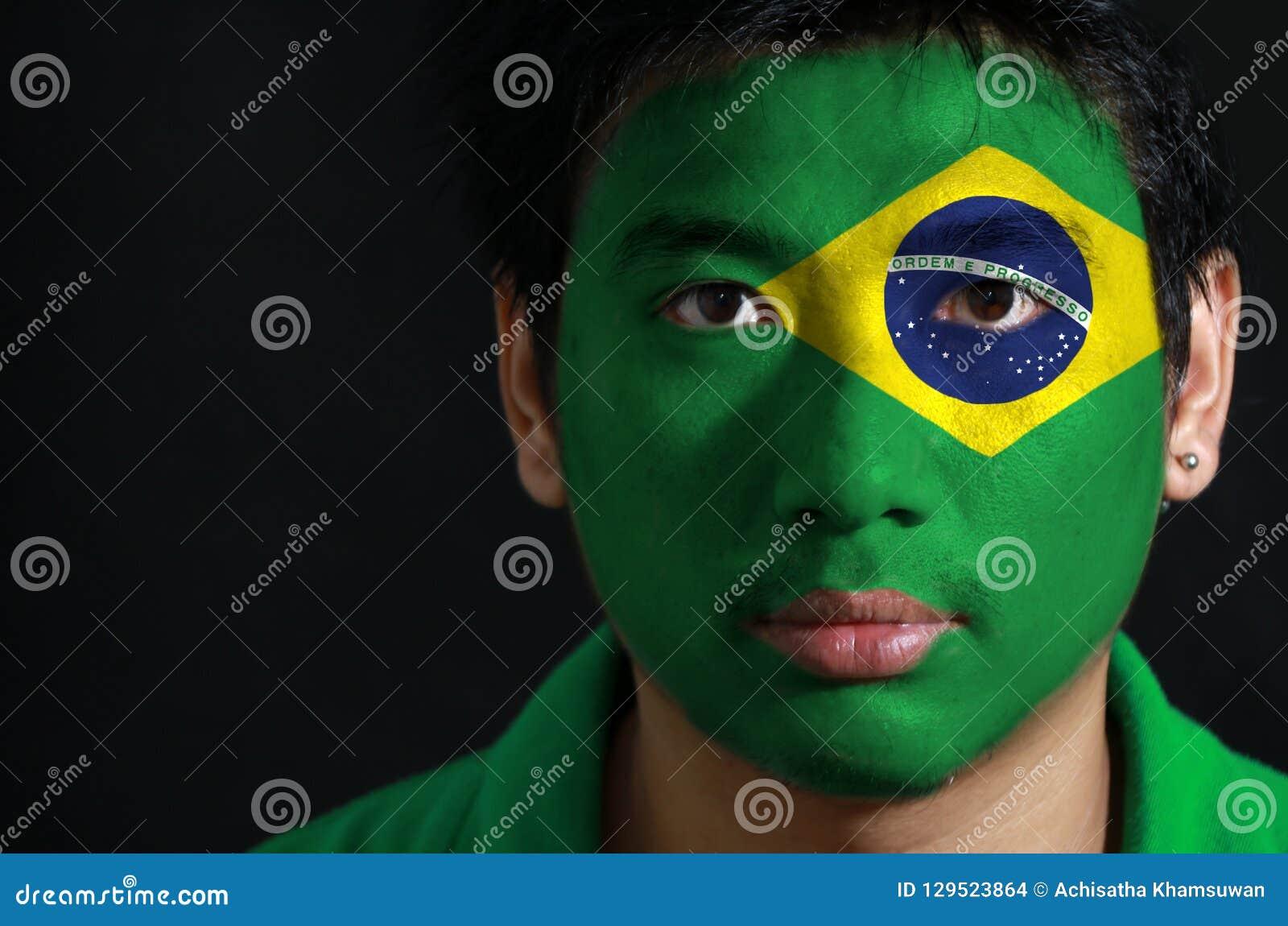 一个人的画象有在他的面孔绘的巴西的旗子的
