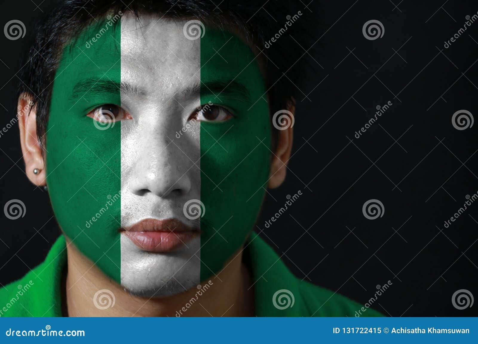 一个人的画象有尼日利亚的旗子的在他的在黑背景的面孔绘了