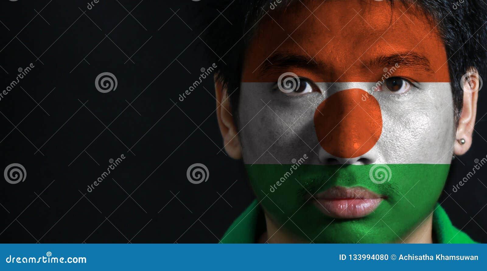 一个人的画象有尼日尔的旗子的在他的在黑背景的面孔绘了