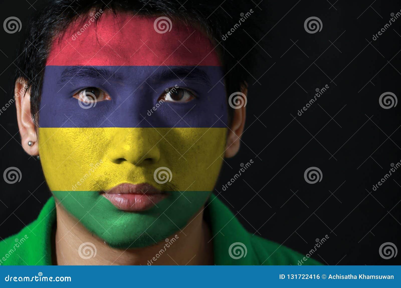 一个人的画象有毛里求斯的旗子的在他的在黑背景的面孔绘了