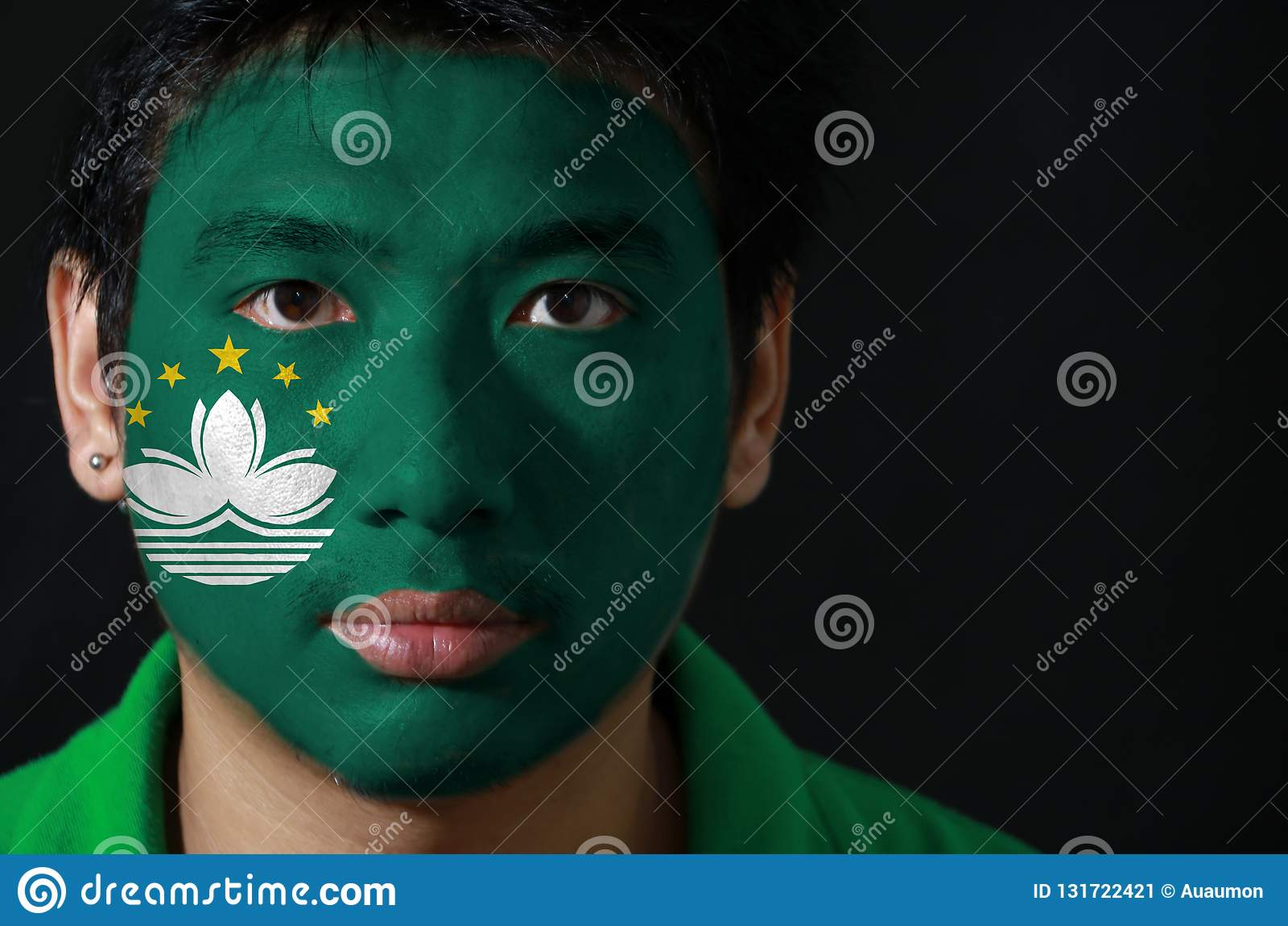 一个人的画象有澳门的旗子的在他的在黑背景的面孔绘了