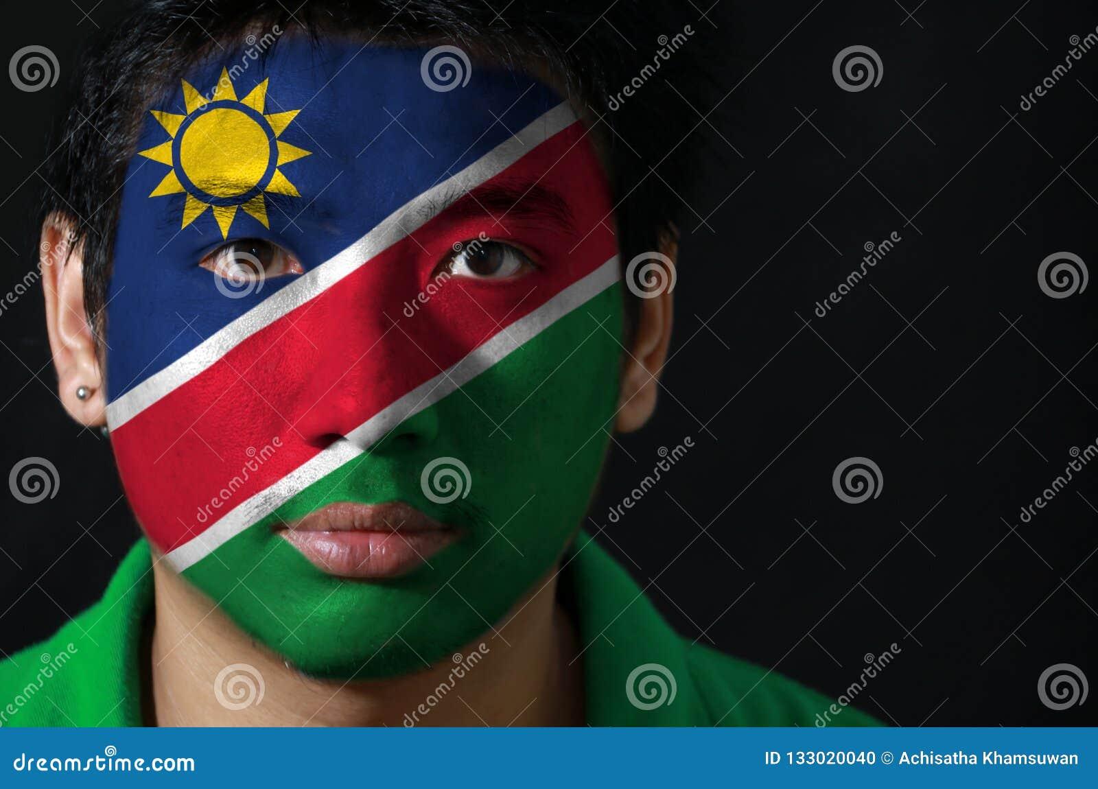 一个人的画象有纳米比亚的旗子的在他的在黑背景的面孔绘了