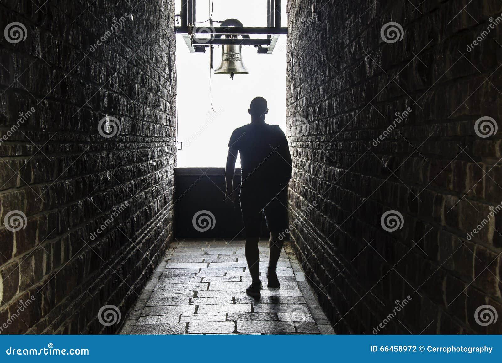 一个人走入一个黑暗的隧道,但是光展示在末端