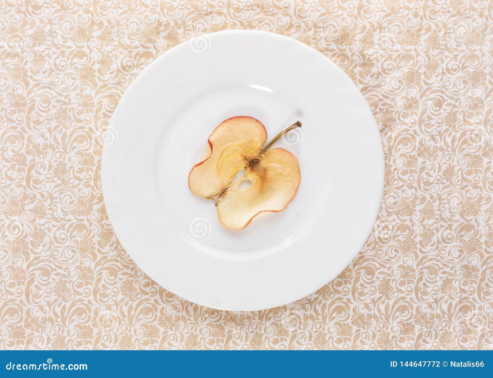 一个切片在白色板材的干苹果在米黄华丽被仿造的背景