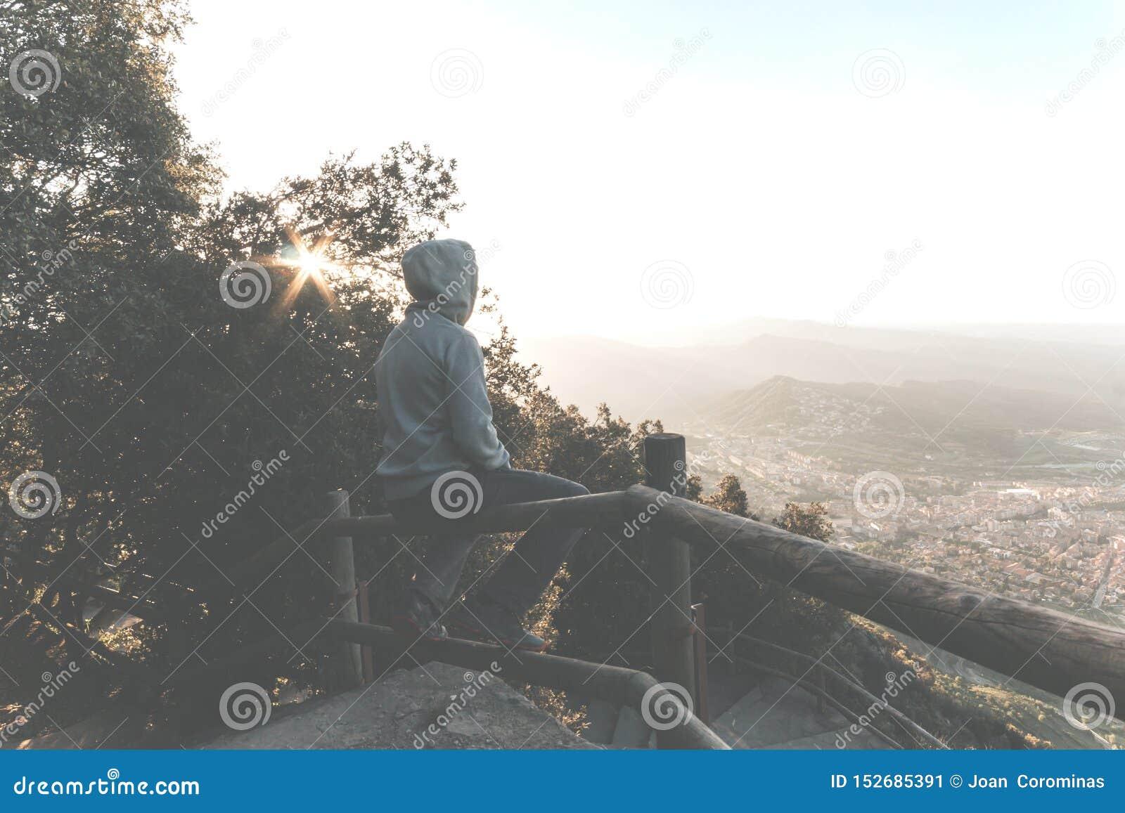 一个哀伤或不快乐的人的画象坐栏杆在日落