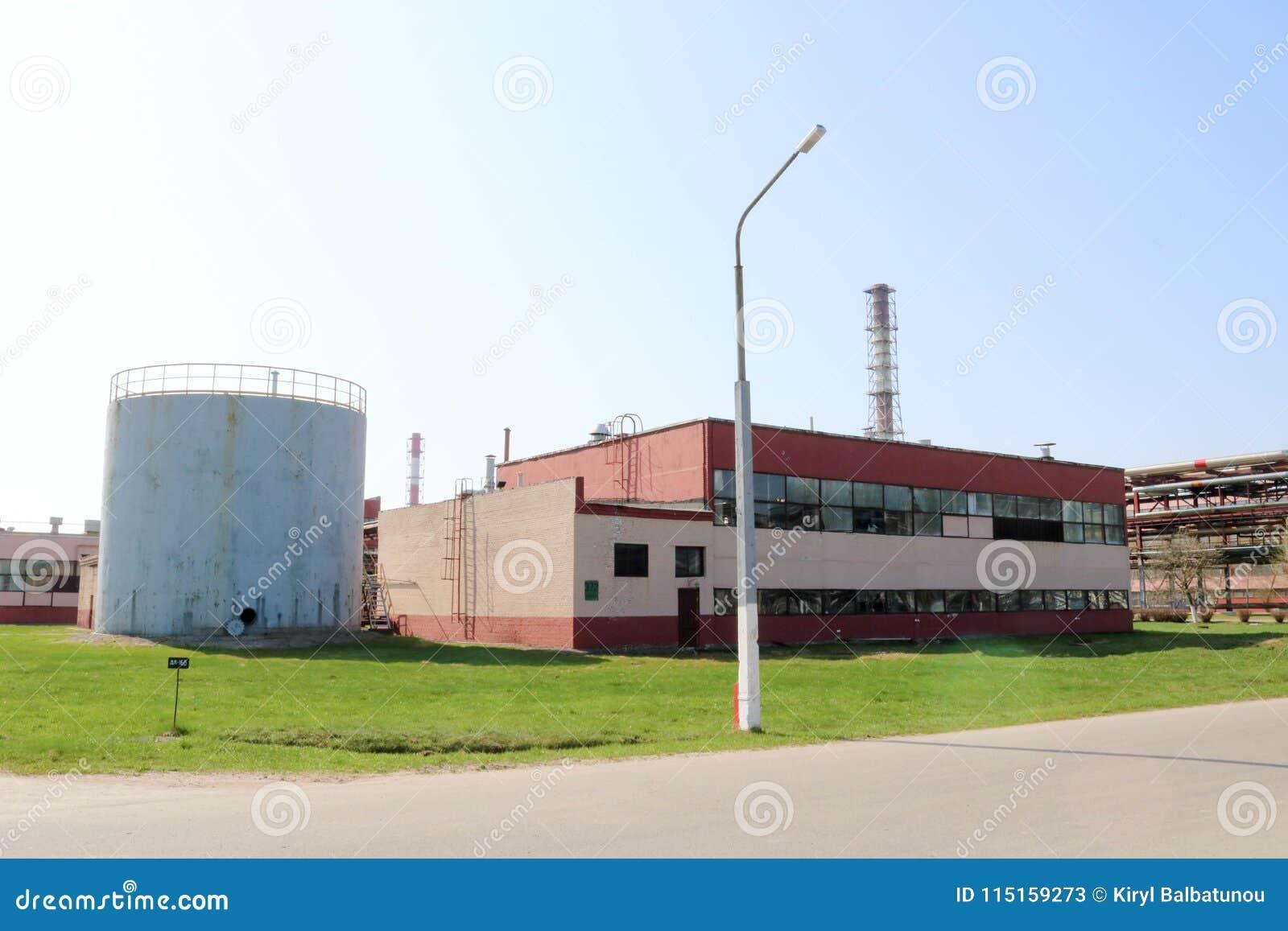 一个大灰色金属容器、桶与一个开放舱口盖和一个红色生产大厦在炼油厂,石油化学制品, chemica