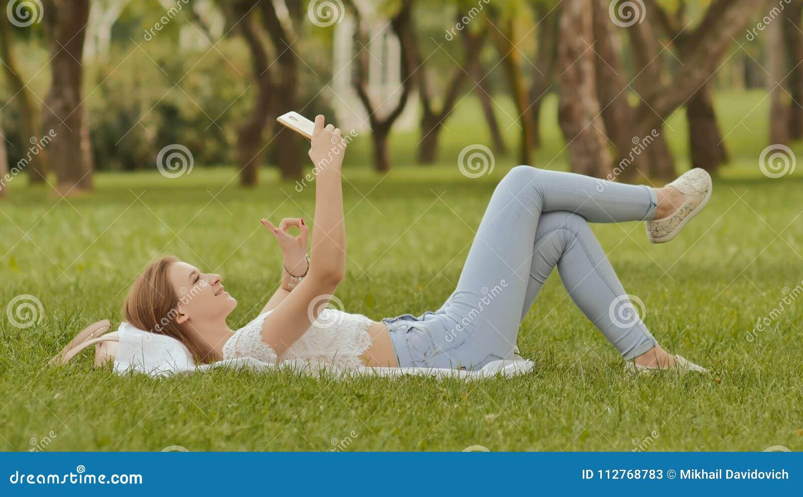 一个女孩在她在与一个智能手机的绿草在她的手上 摆在照相机电话的乐趣 重新创建