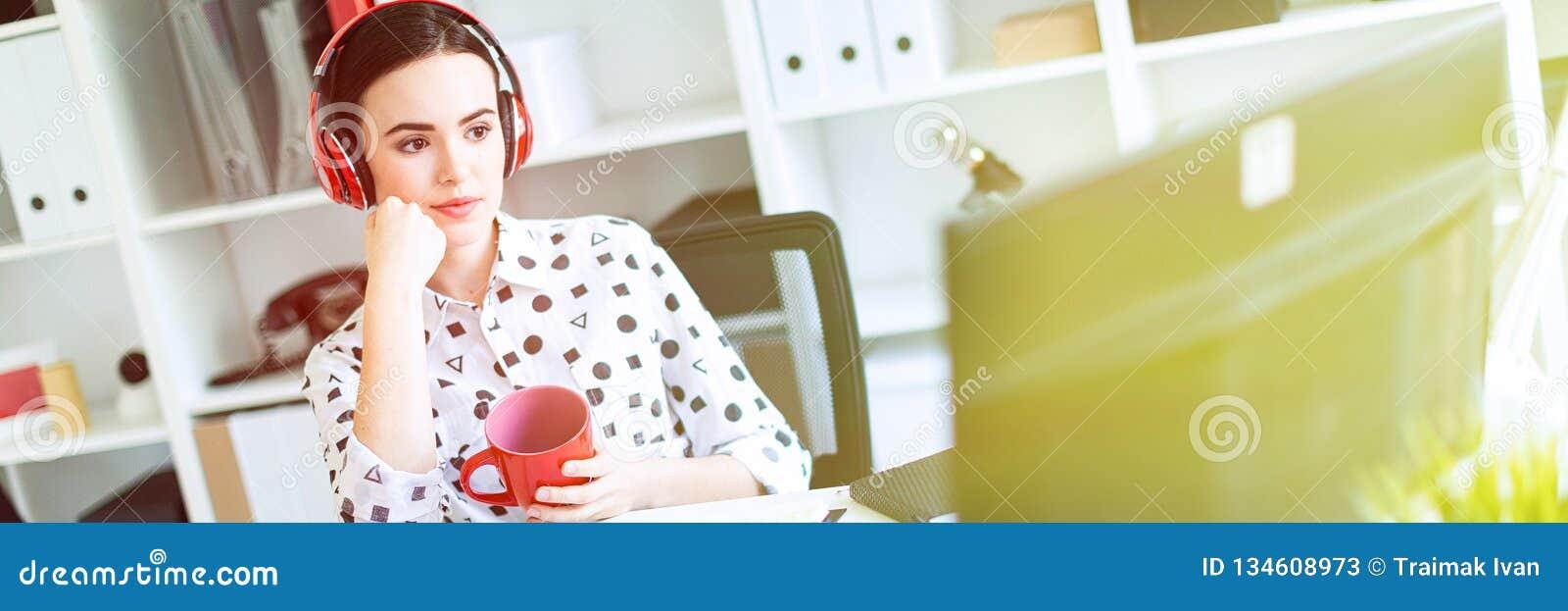 一个女孩在耳机在她的手上坐在一张桌上在办公室,拿着一个红色杯子并且看显示器