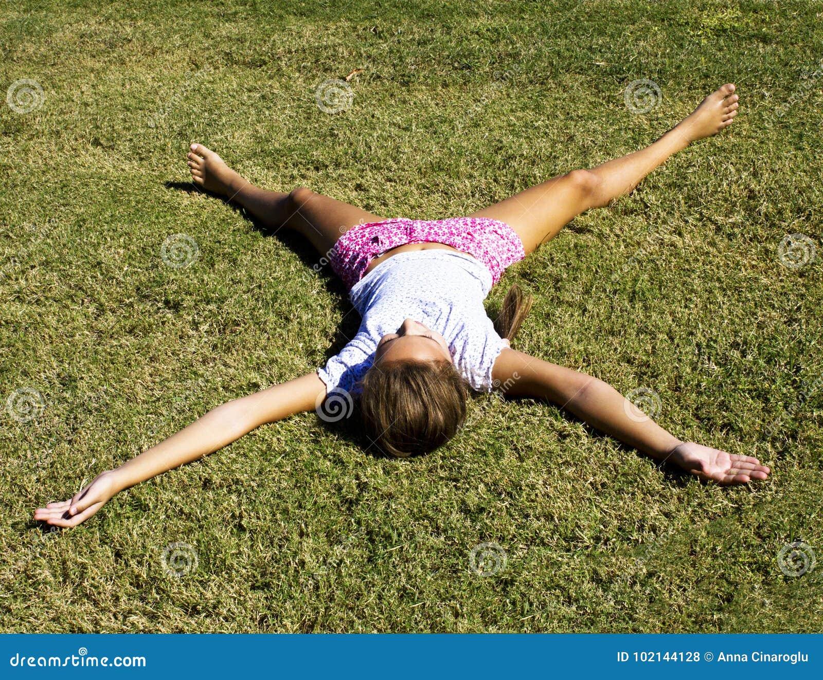 一个女孩在舒展她的胳膊和腿的被割的草说谎