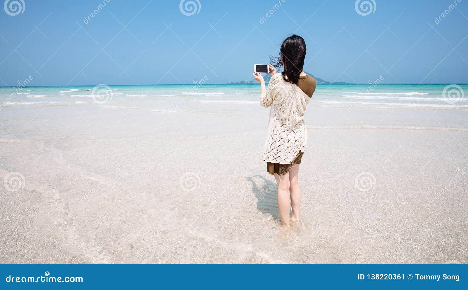 一个女性旅客拍绿松石海洋的照片有手机照相机济州岛的